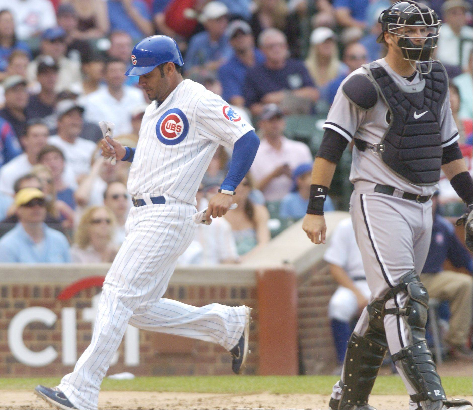 Carlos Pena of the Cubs scores during the second inning as White Sox catcher A.J. Pierzynski stands at the plate Friday.