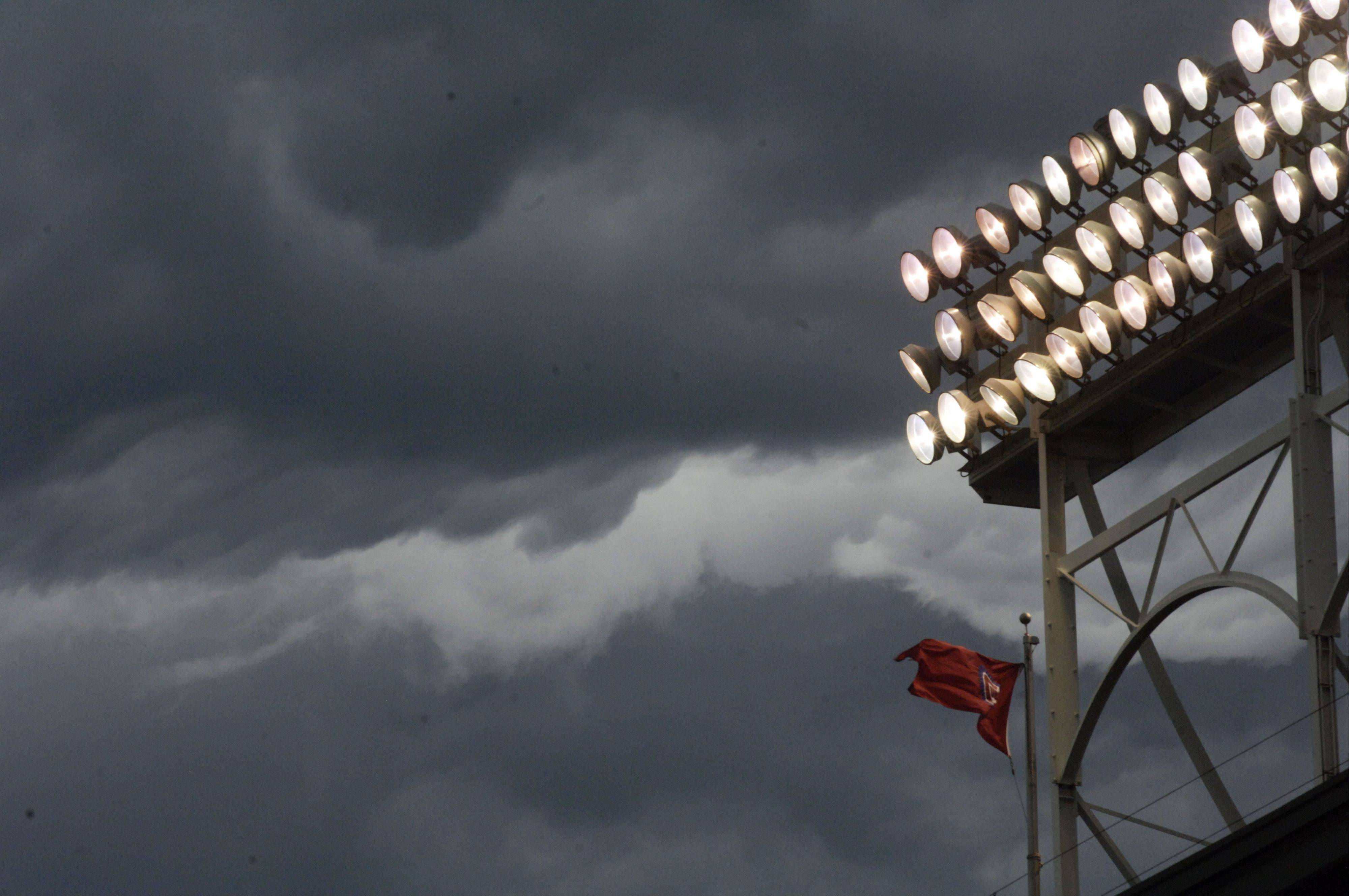 The flags blow in a stiff wind under threatening skies before Friday's game between the Cubs and White Sox at Wrigley Field.