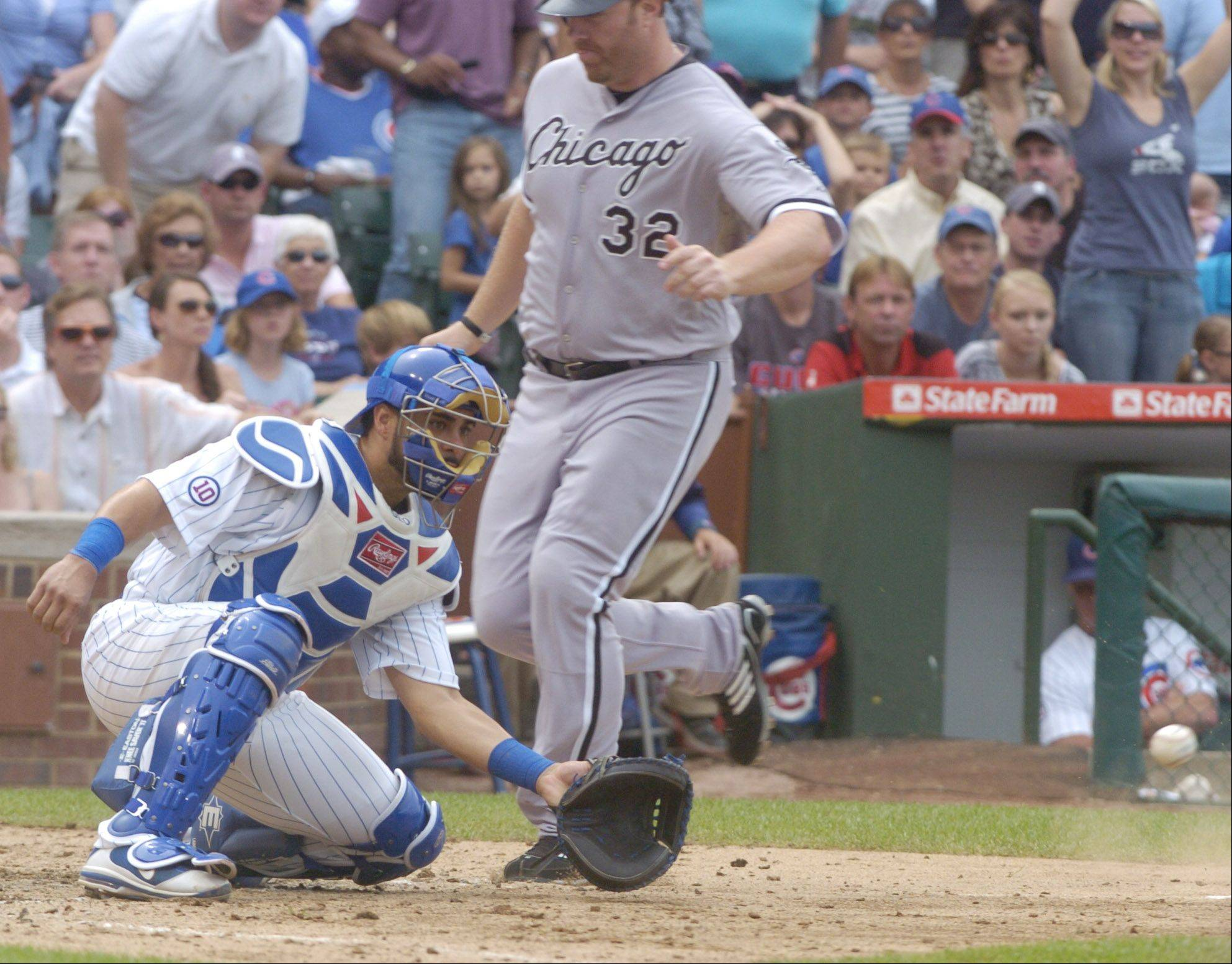Adam Dunn of the White Sox scores on a two-run triple by Juan Pierre of the White Sox as Cubs catcher Geovany Soto takes the late throw during Friday's game.