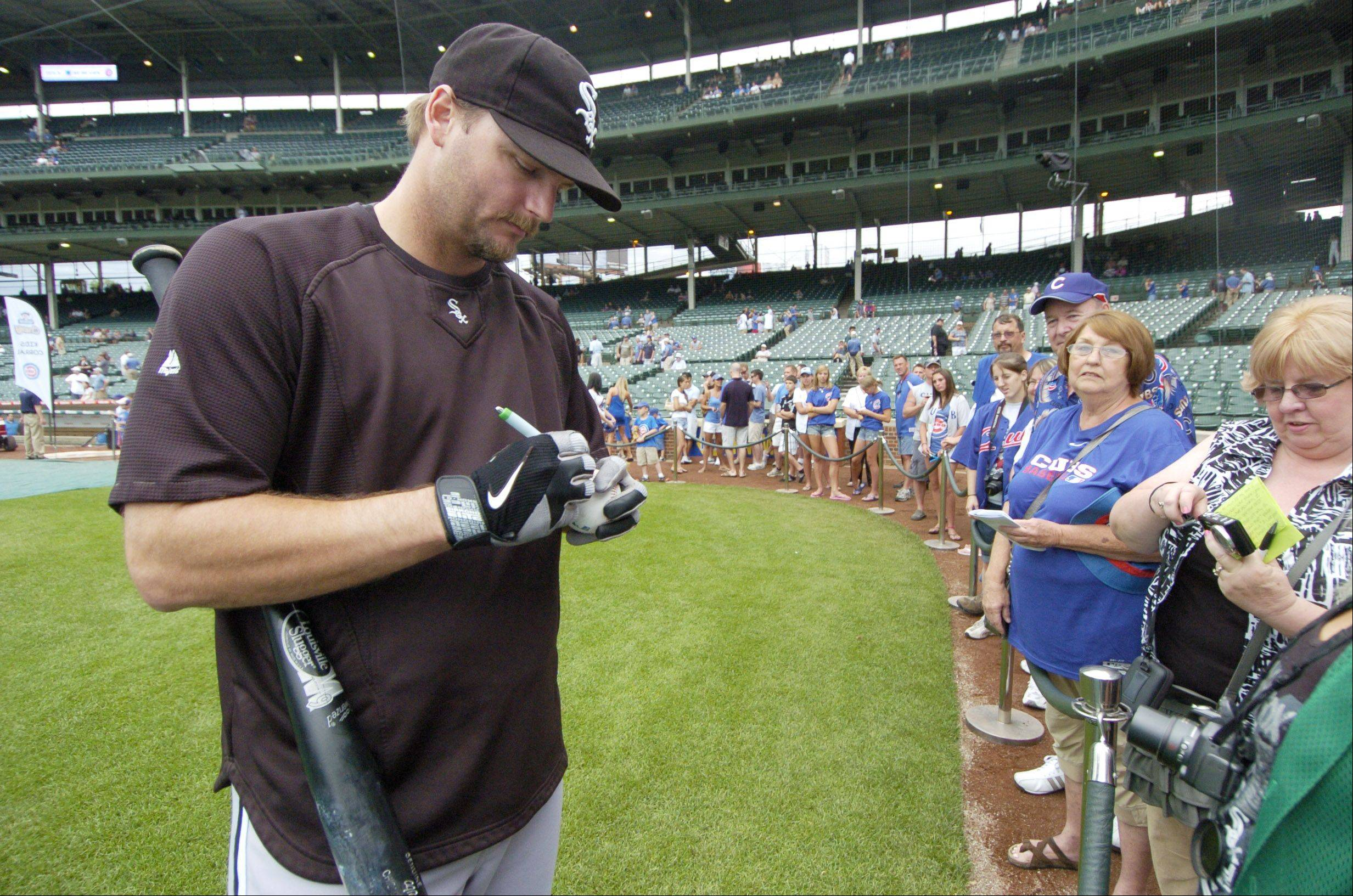 Chicago White Sox catcher A.J. Pierzynski signs autographs for a group that includes mostly Cubs fans at Wrigley Field Friday.