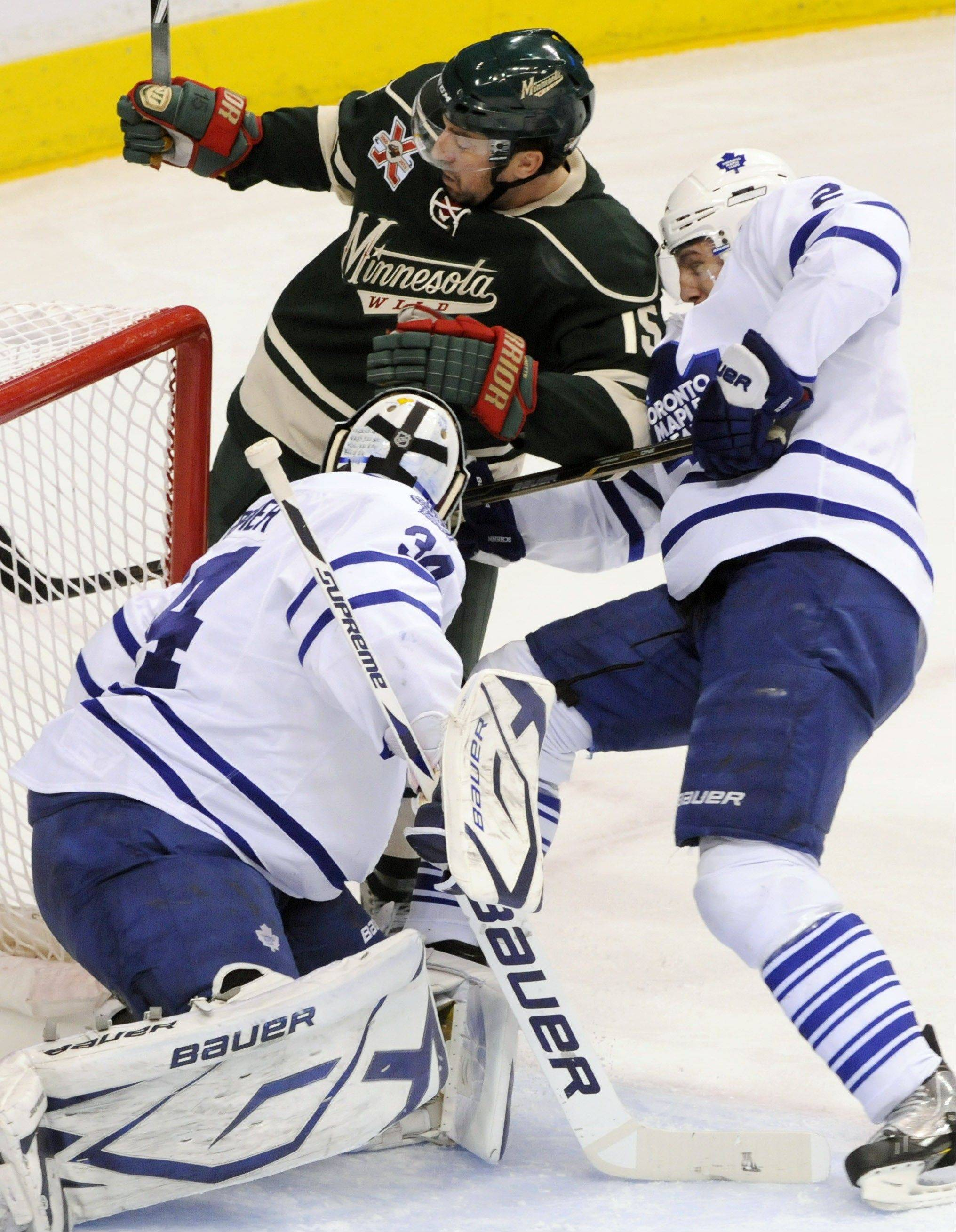 Toronto Maple Leafs' Luke Schenn, right, helps goalie James Reimer defend the net against Minnesota's Andrew Brunette last March. The Blackhawks signed the gritty Brunette on Friday.