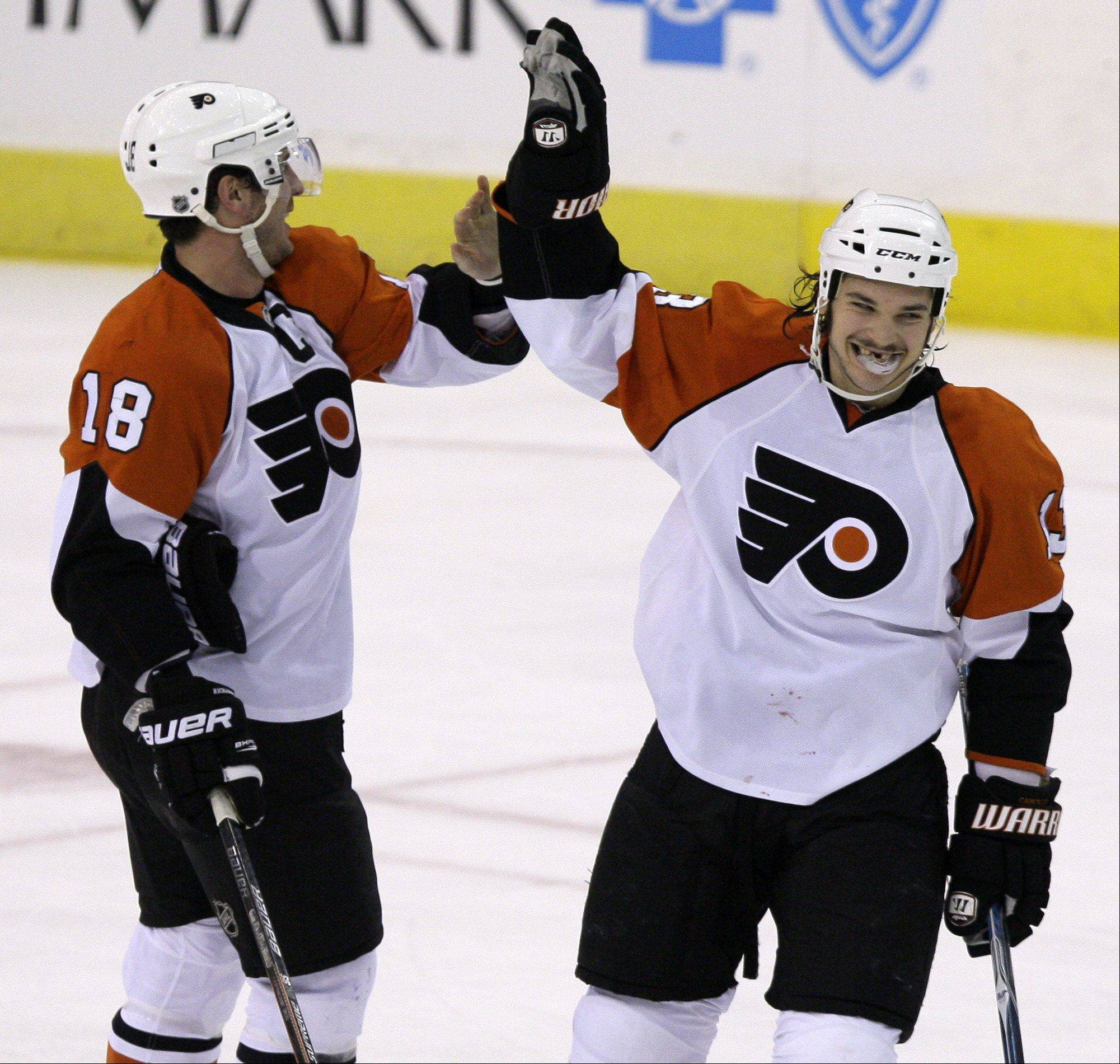 Philadelphia Flyers' Dan Carcillo, right, celebrates with teammate Mike Richards (18) after scoring in the first period against the Pittsburgh Penguins during an NHL hockey game in Pittsburgh on Tuesday, Dec. 15, 2009.