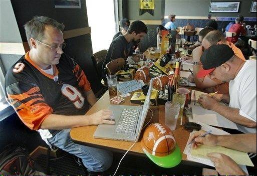 Brian Sherman, left, uses his laptop to record moves in his team�s fantasy football draft last August at a Buffalo Wild Wings restaurant in Cincinnati. As NFL owners and players wrestle over how to split $9.3 billion in revenue, pro football�s lockout has already cut into the widely popular, $800-million per year fantasy football industry.