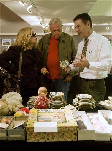 Edwin Walker, right, a professor at Millikin University and personal property appraiser, speaks to Doug Gross and Jacqueline Ames about antique china dishes during a sale in May.