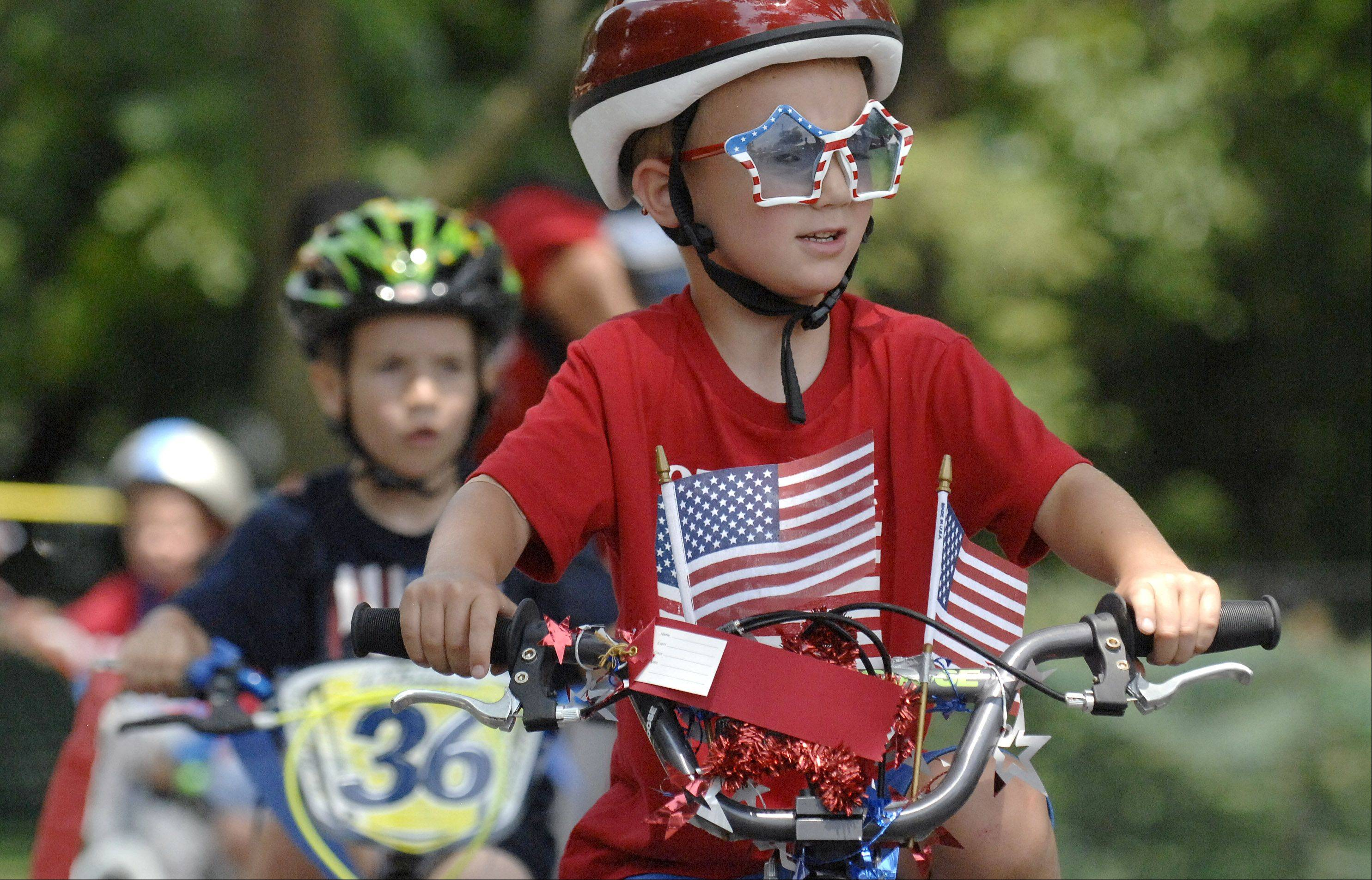 Charlie Carnes, 5, of Crystal Lake, shows off his patriotic side during a kids decorated bike parade at the Lakeside Festival. Charlie's brother, Ben, 8, also participated in the ride. The festival is running through the weekend at Lakeside Legacy Arts Park.