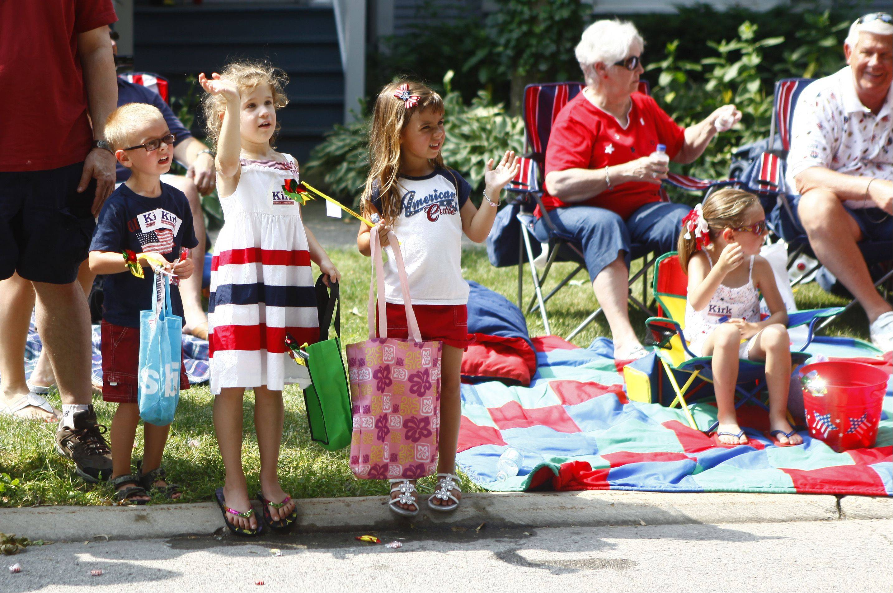 Jonathan Kravchuk, 5, Chloe Gross, 5, and Julia Kravchuk, 5, all from Rolling Meadows, wave to floats passing during the annual Palatine Jaycees Independence Day Parade Saturday morning. For more on the festivities across the area, see Page X.
