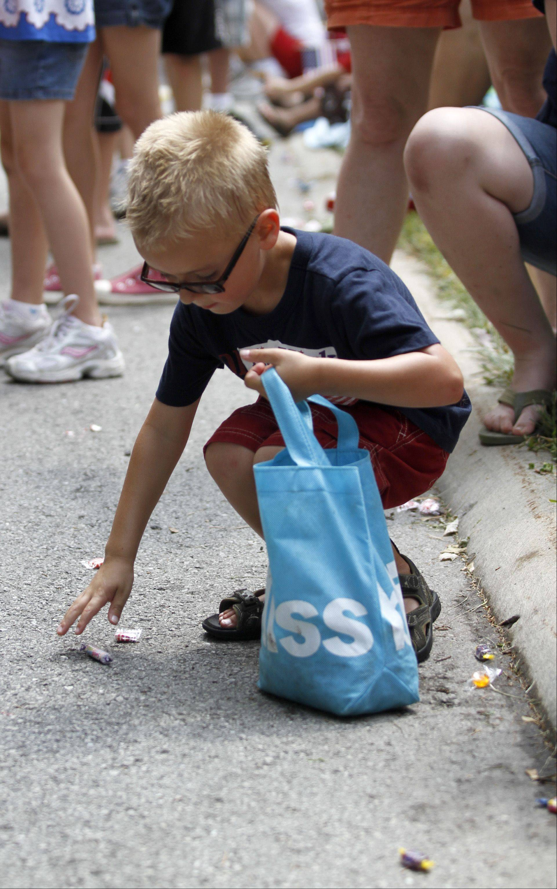 Jonathan Kravchuk, 5, from Rolling Meadows, picks up candy thrown toward him during the annual Palatine Jaycees Independence Day Parade Saturday morning.