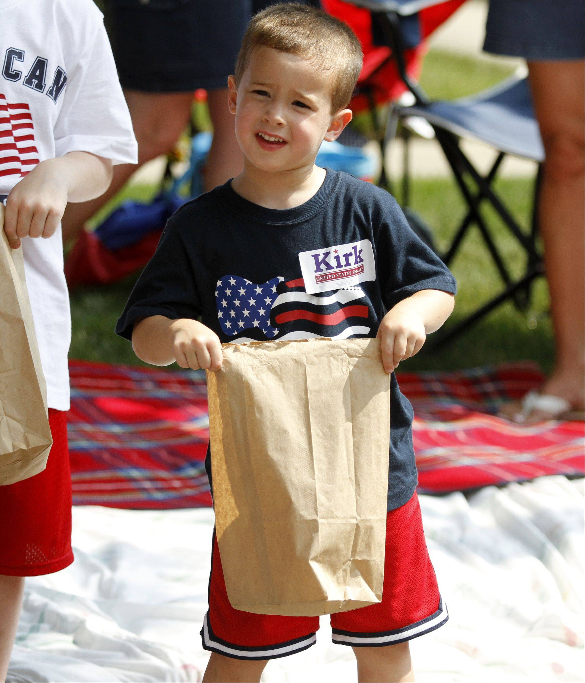 Four-year-old Dennis Bond, from Palatine, waits on the side of the street for candy to be thrown during the annual Palatine Jaycees Independence Day Parade Saturday morning.