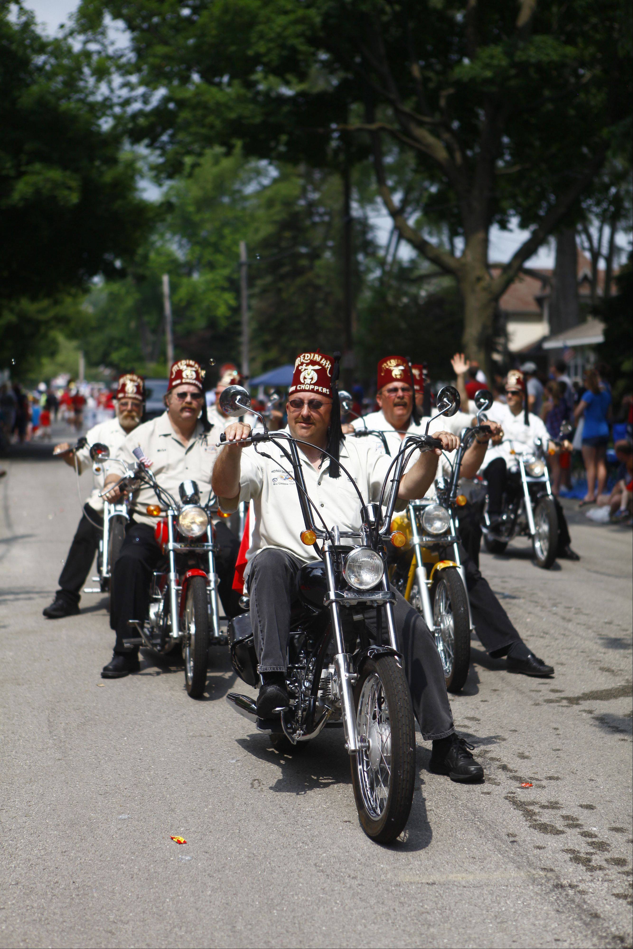 Members of the Shriners club ride past the crowd on motorcycles during the annual Palatine Jaycees Independence Day Parade Saturday morning.
