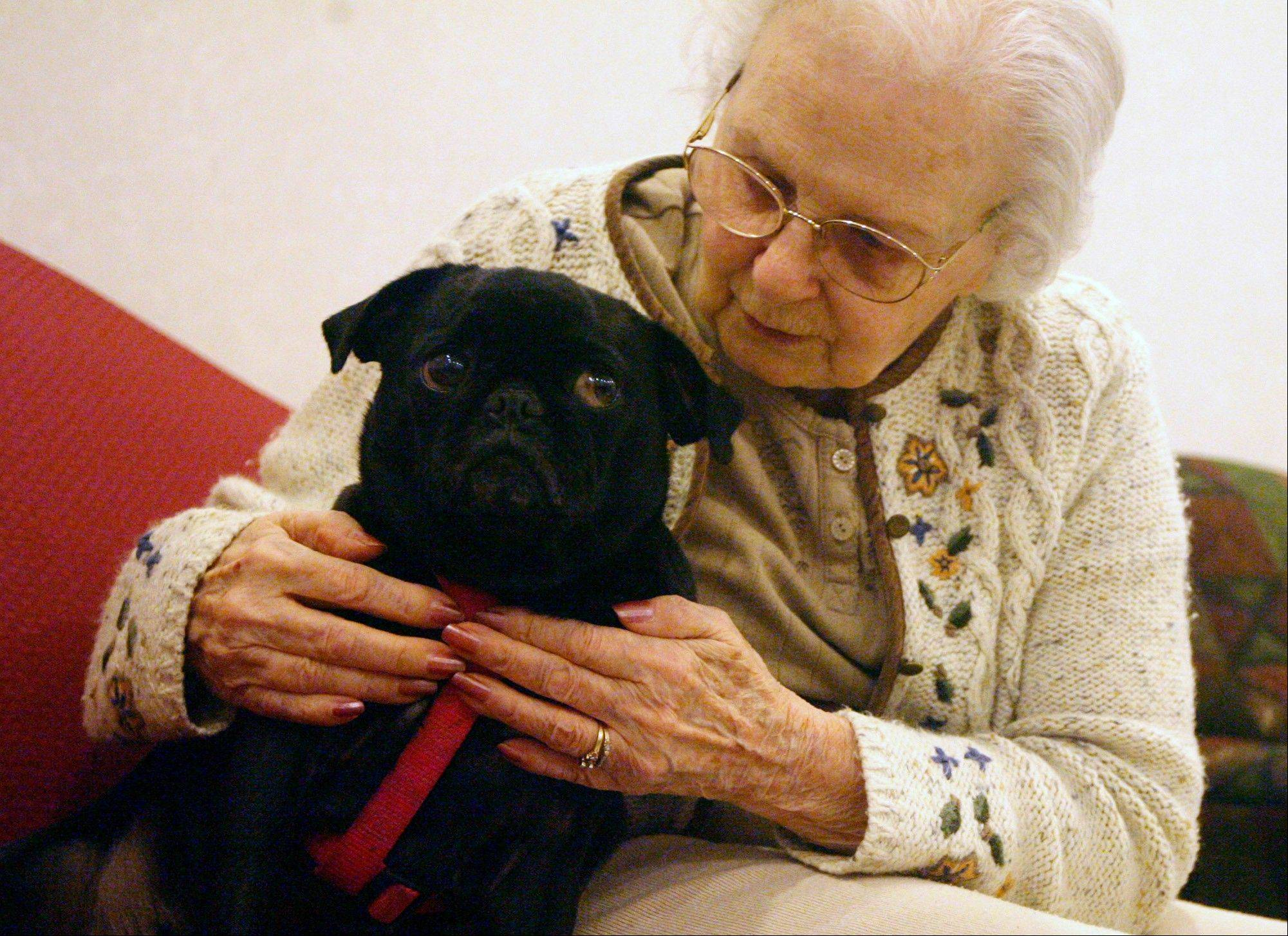 Allie snuggles with North Adams Home Special Care Unit resident Mary Ellen Martin in Mendon, Ill.
