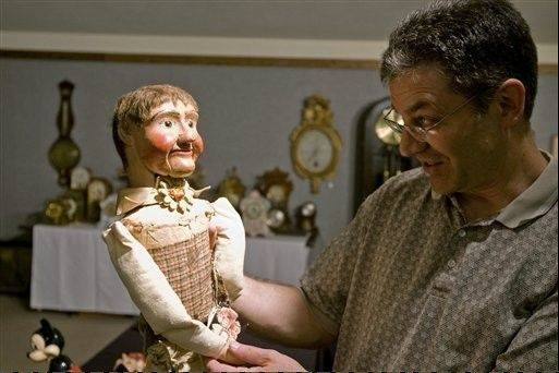 Edwin Walker examines an old, wooden ventriloquist doll in Decatur, Ill. Walker is an accredited member of the International Society of Appraisers. You pay him to price antiquities, and he sticks rigorously to an honesty-is-the-best-policy approach.