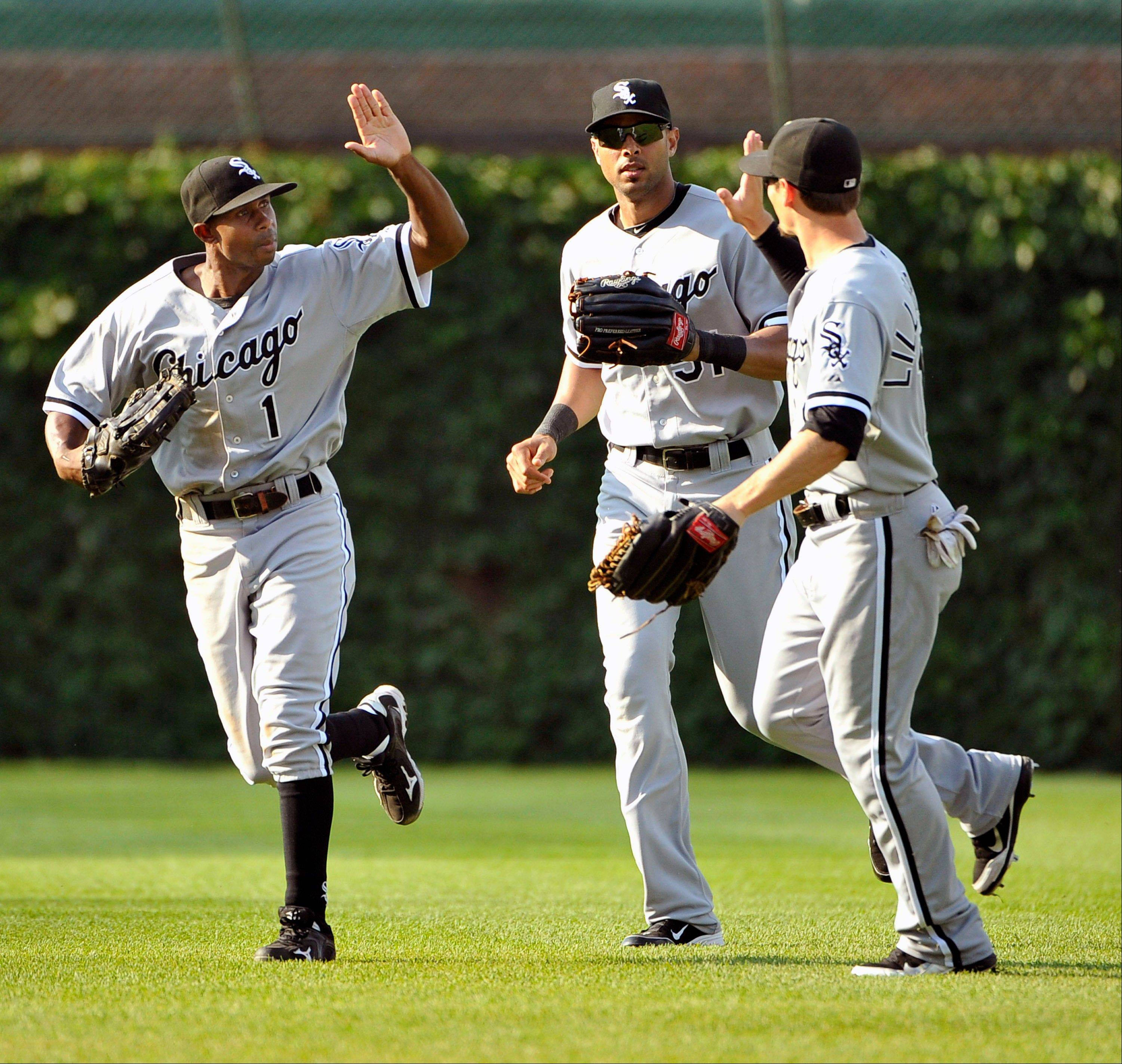 White Sox outfielders Juan Pierre, from left, Alex Rios and Brent Lillibridge celebrate after Saturday's victory at Wrigley Field.