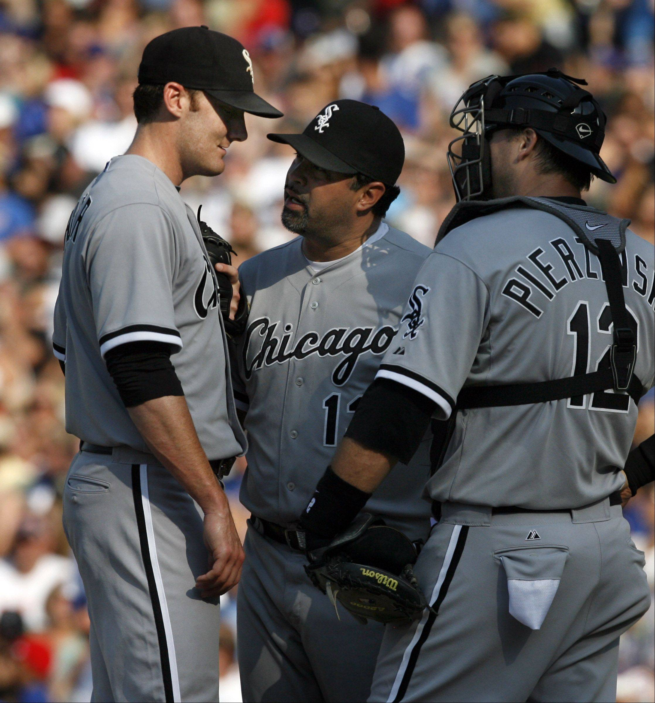 White Sox manager Ozzie Guillen talks to pitcher Philip Humber and catcher A.J. Pierzynski late in the game against the Cubs at Wrigley Field on Saturday.