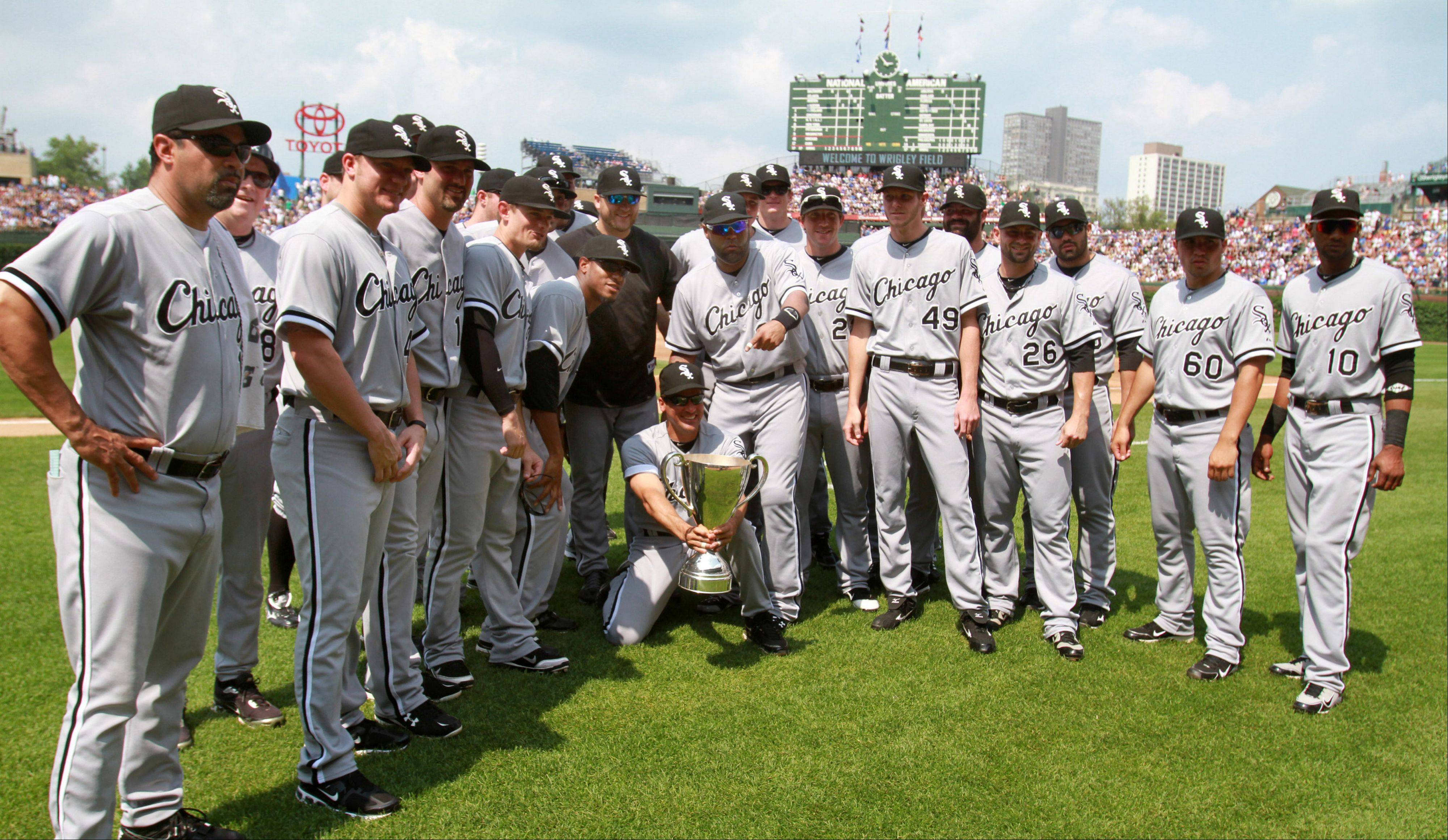 White Sox manager Ozzie Guillen and the team pose a photo with the BP Cup before the game with the Cubs at Wrigley Field on Saturday.