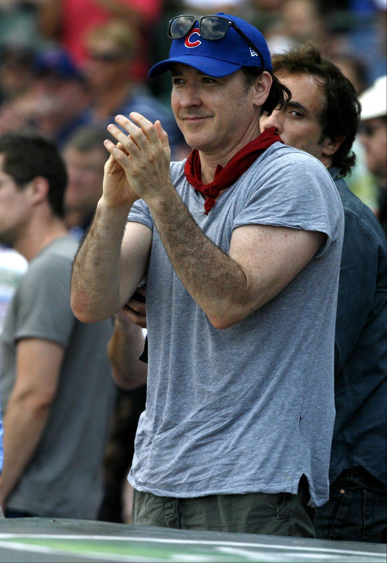 Actor John Cusack gives the Cubs a hand during the ninth inning in 1-0 lose over White Sox at Wrigley Field on Saturday.