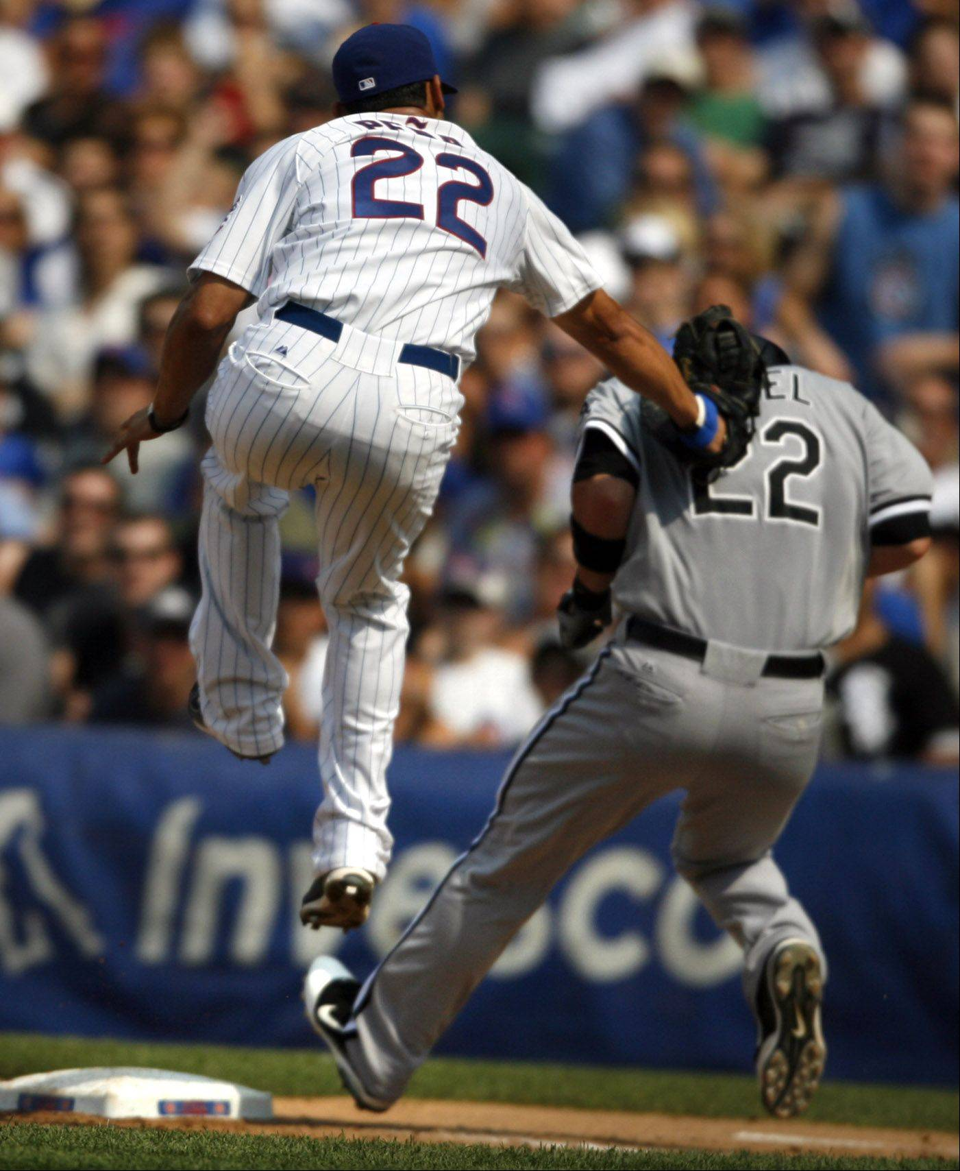 Cubs Brent Morel, in mid air, tags White Sox Carlos Pena out at first at Wrigley Field on Saturday.