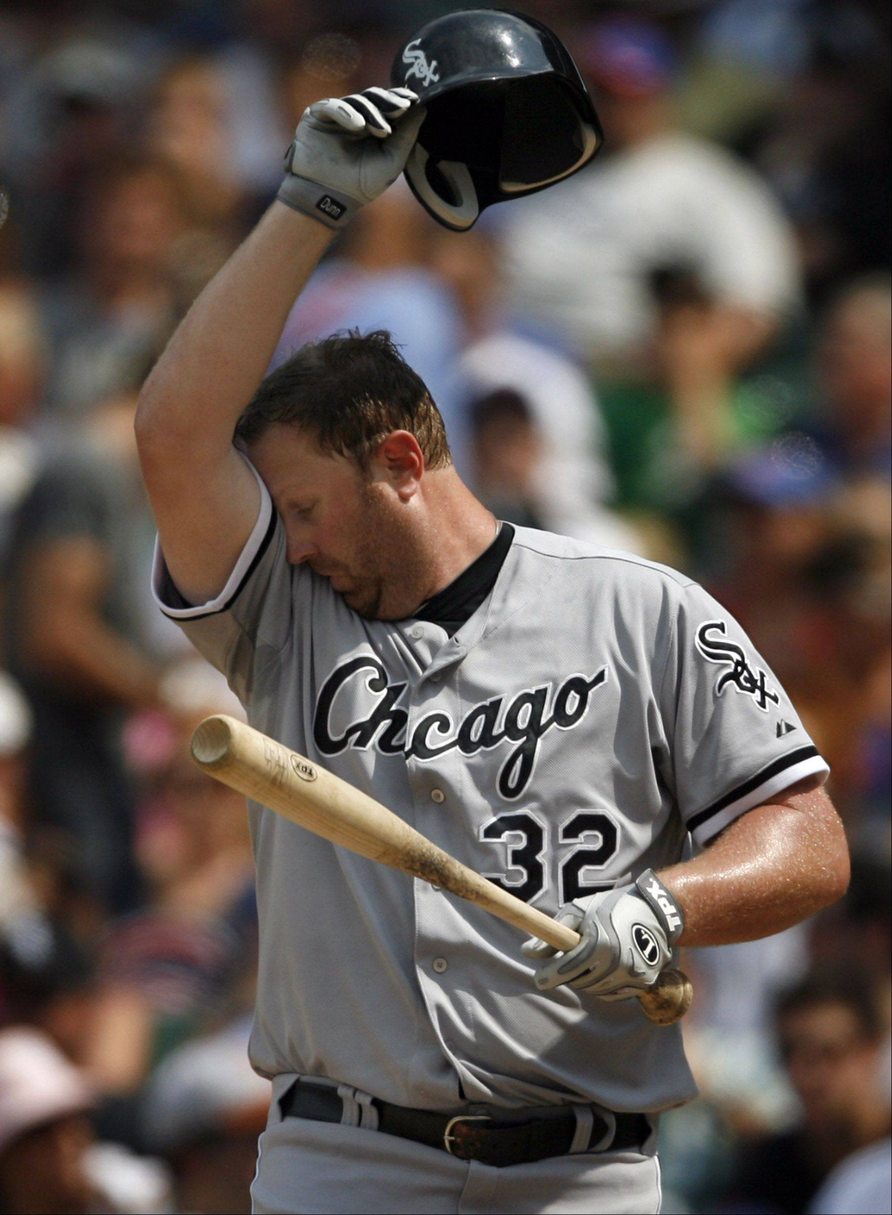 White Sox Adam Dunn wipes his forehead after striking out as Sox win 1-0 at Wrigley Field on Saturday.