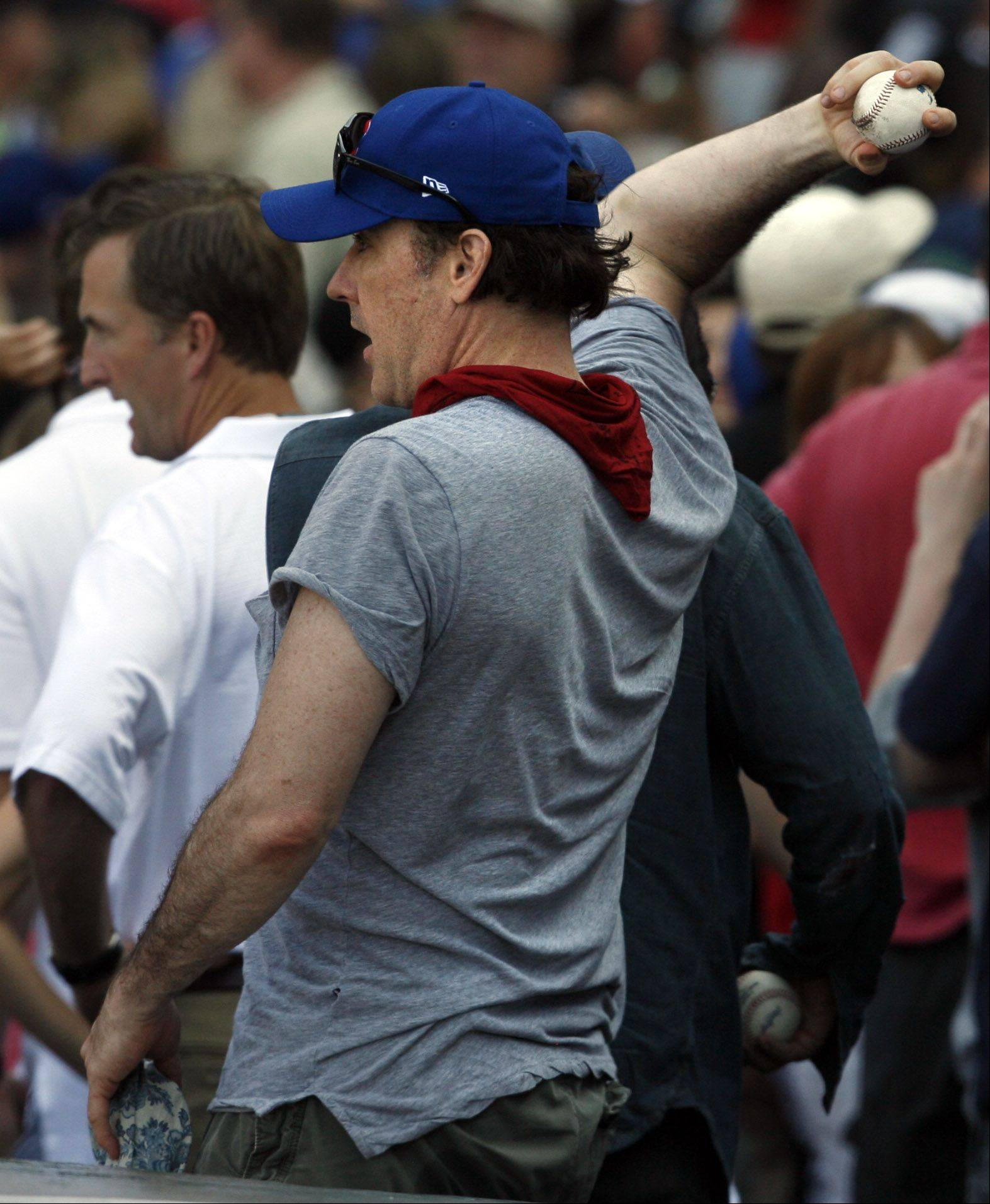 Actor John Cusack pretend to throw a ball on the field as Cubs lose 1-0 against the White Sox at Wrigley Field on Saturday.