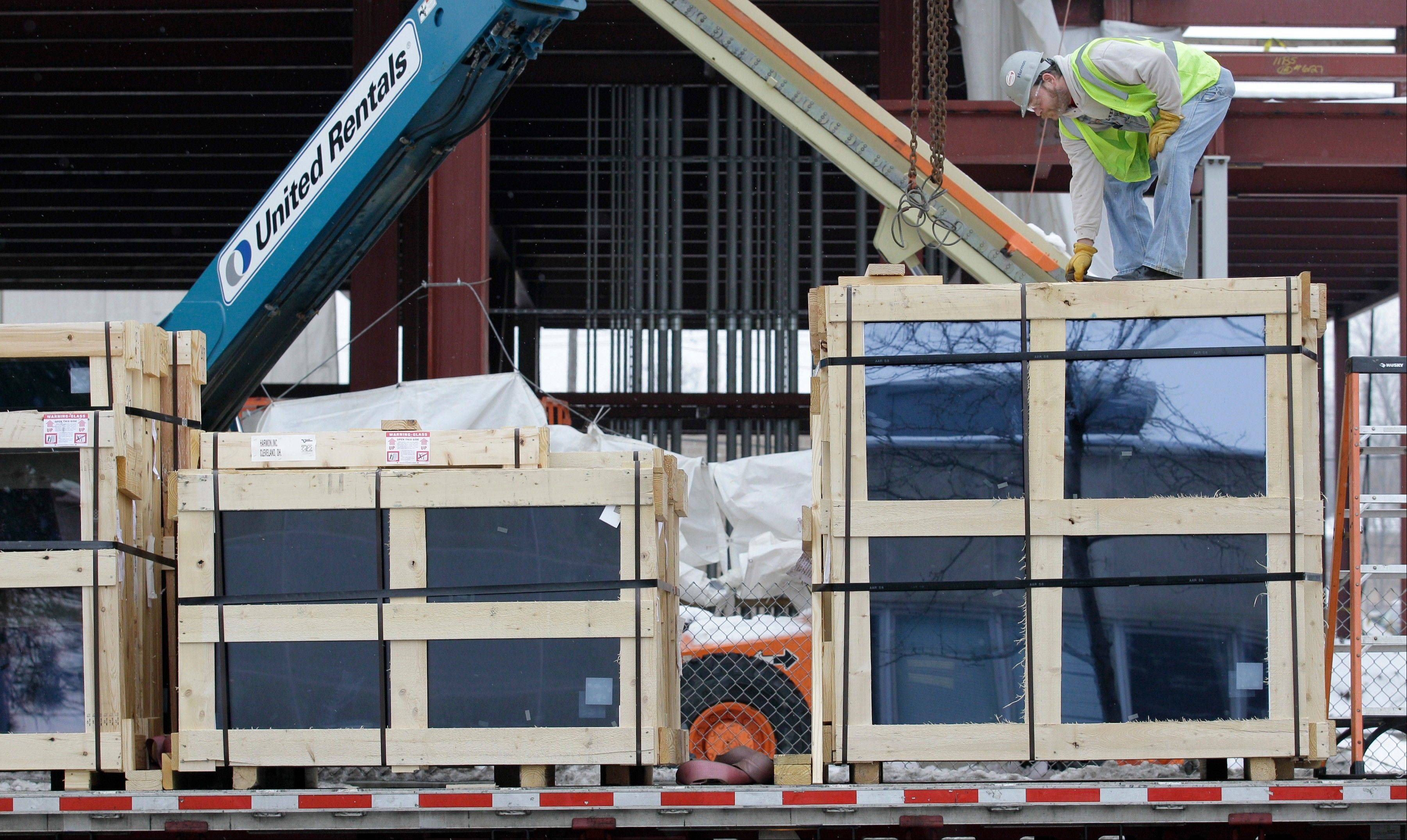 A construction worker unpacks a crate of glass panels for use in a new piece of Cleveland Clinic construction in Cleveland. The future of real estate investing may be less about owning property and more about buying the stocks of real estate investment trusts.