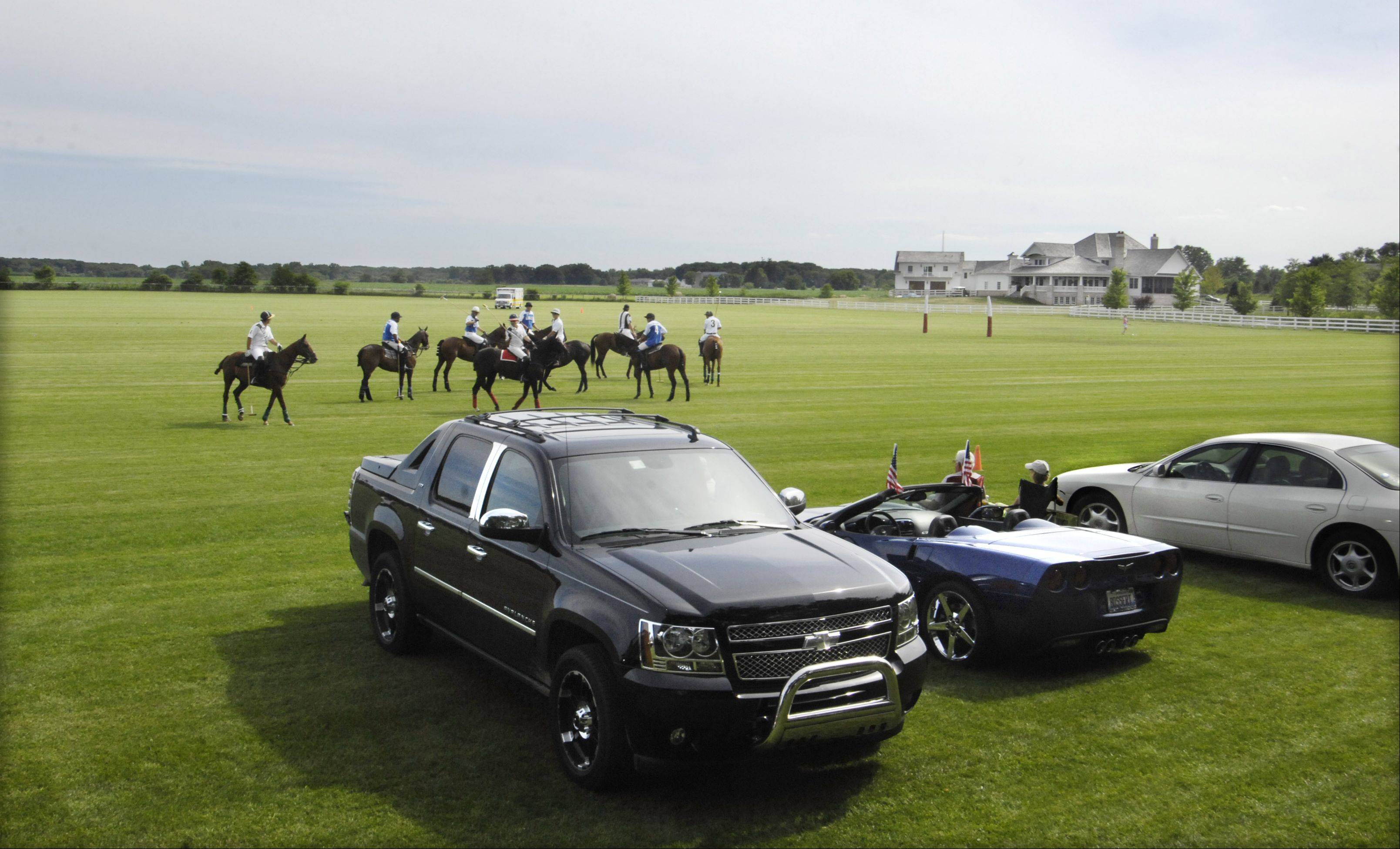 Players and their mounts gather for a restart near the sidelines where the ball went out of bounds Sunday during the finals of the Freemont Cup at the Dahlwood Polo Farm, west of Elgin.