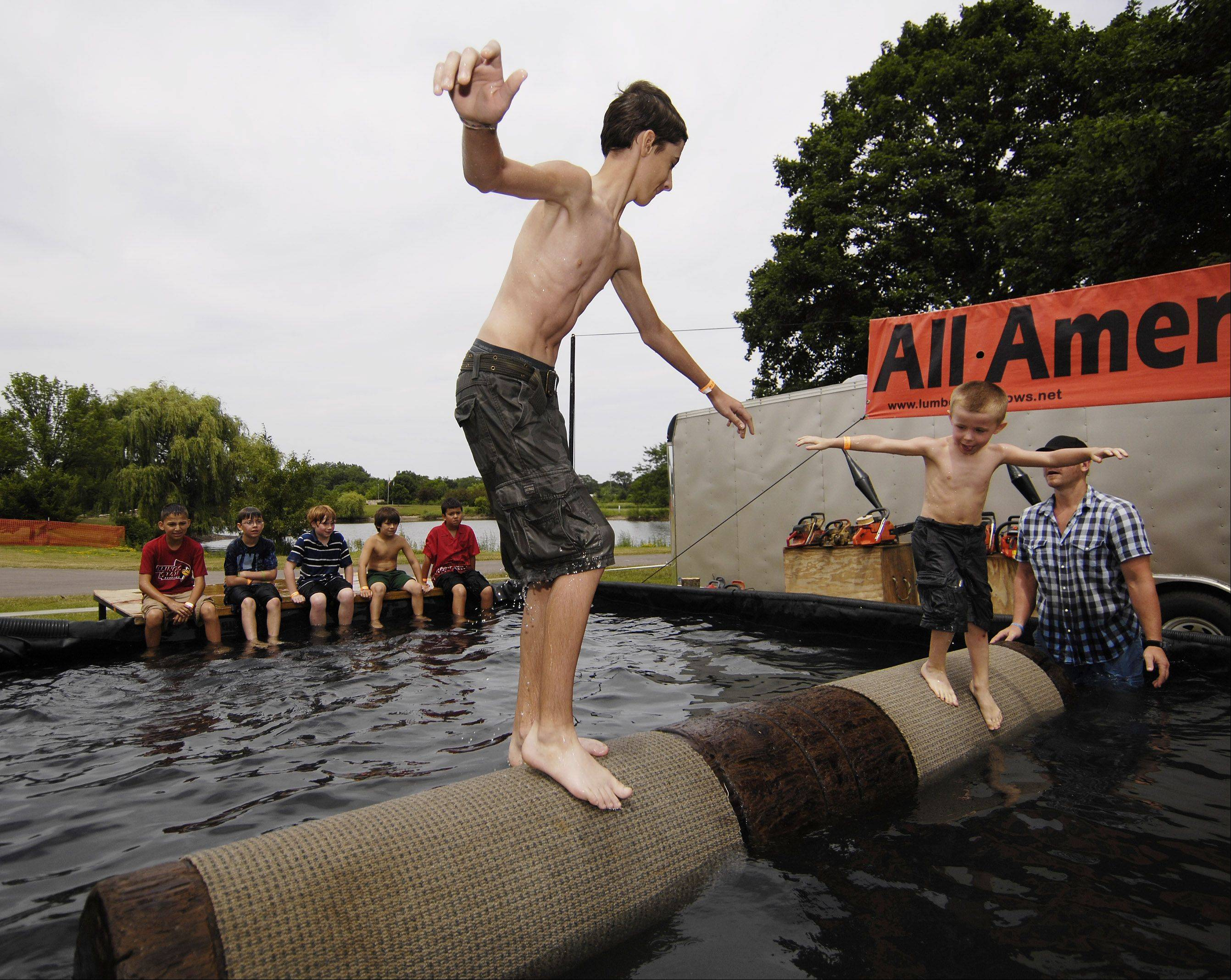 Justin, 15, and Logan Fernandes, 5, of Lisle, try out log rolling at the Eyes to the Skies Festival in Lisle Sunday.