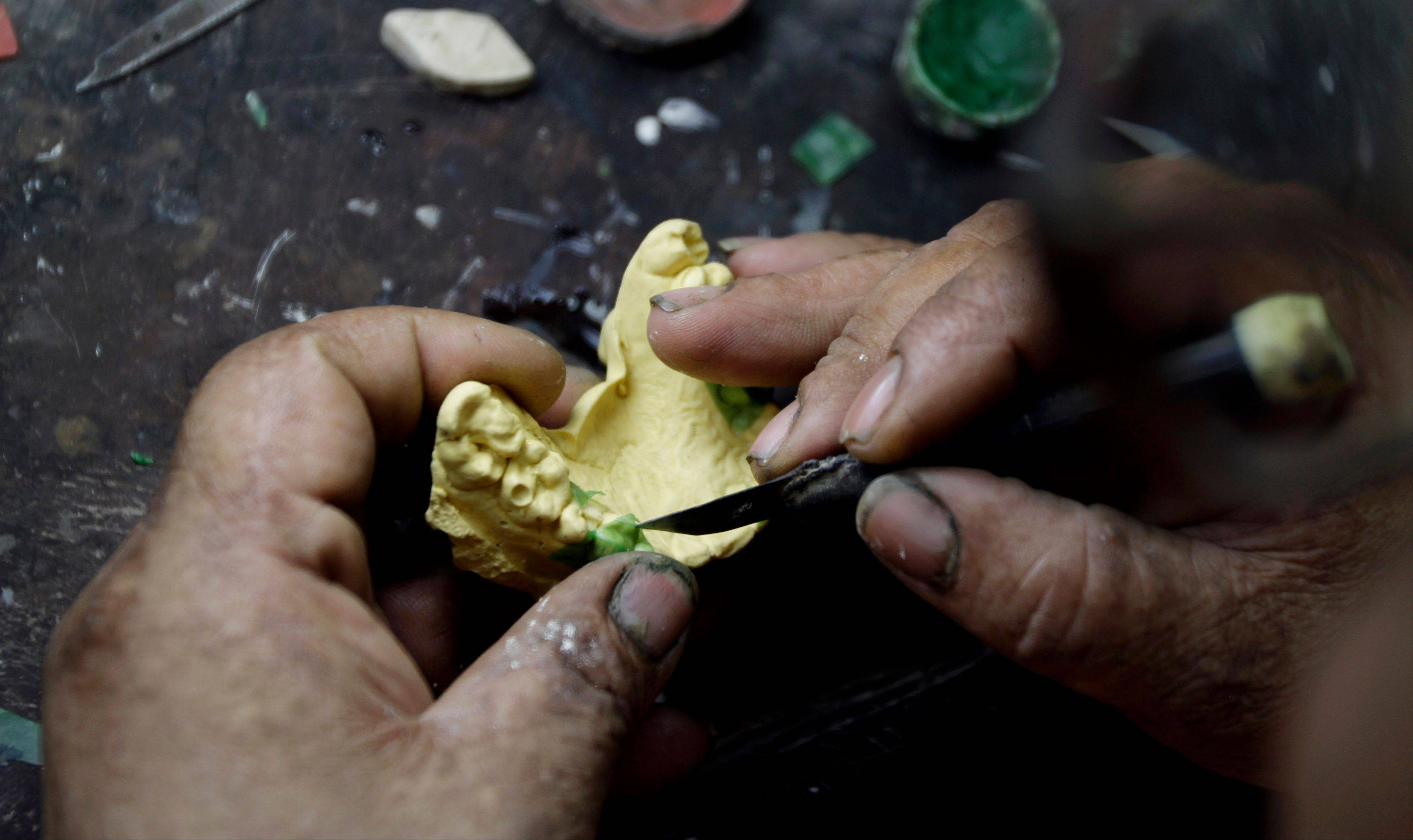 In this June 20, 2011 photo, a man who did not want to be identified molds a tooth with wax in order to make a gold tooth in his workshop in Havana. One goal of Cuban President Raul Castro's economic opening is to legalize at least a portion of the black market so that those making a living from it will register themselves with authorities and pay taxes, and there is some evidence it is working. However, the sale of gold is regulated, so those who melt it down for use in false teeth are not able to get licenses and continue to be part of the black market. The tooth maker charges up to $40 per tooth, including installation, using gold melted down from jewelry and trinkets he buys from secret suppliers. (AP Photo/Franklin Reyes)