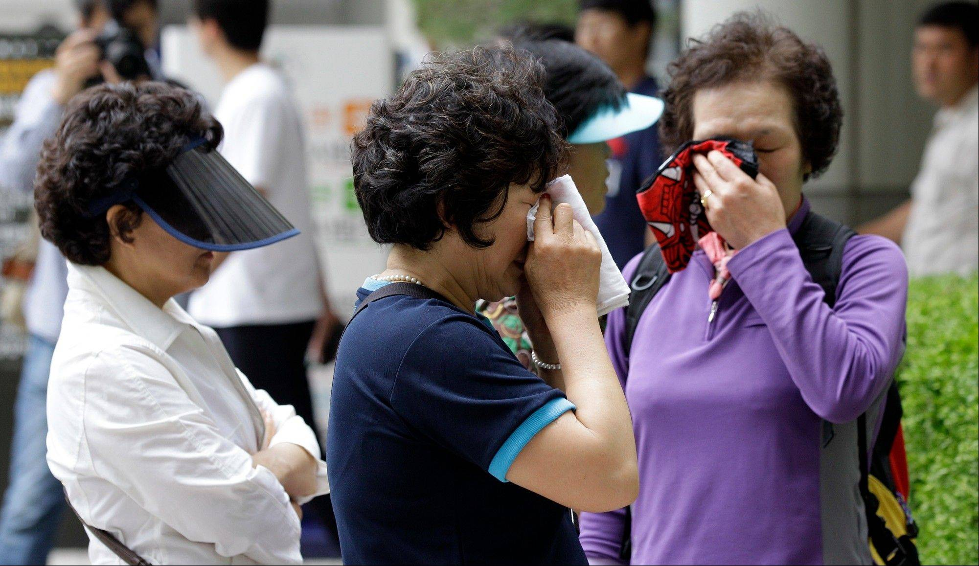 South Korean clients of the suspended Busan Savings Bank wipe their tears after they watched a trial for the bank�s corruption at Seoul Central District Court in Seoul, South Korea, in June.