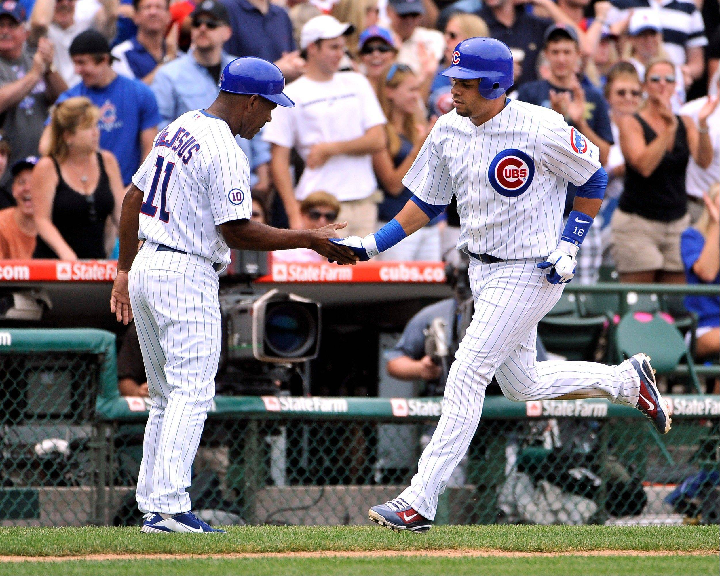 Cubs third-base coach Ivan DeJesus congratulates Aramis Ramirez as he rounds the bases after hitting a two-run homer Sunday.