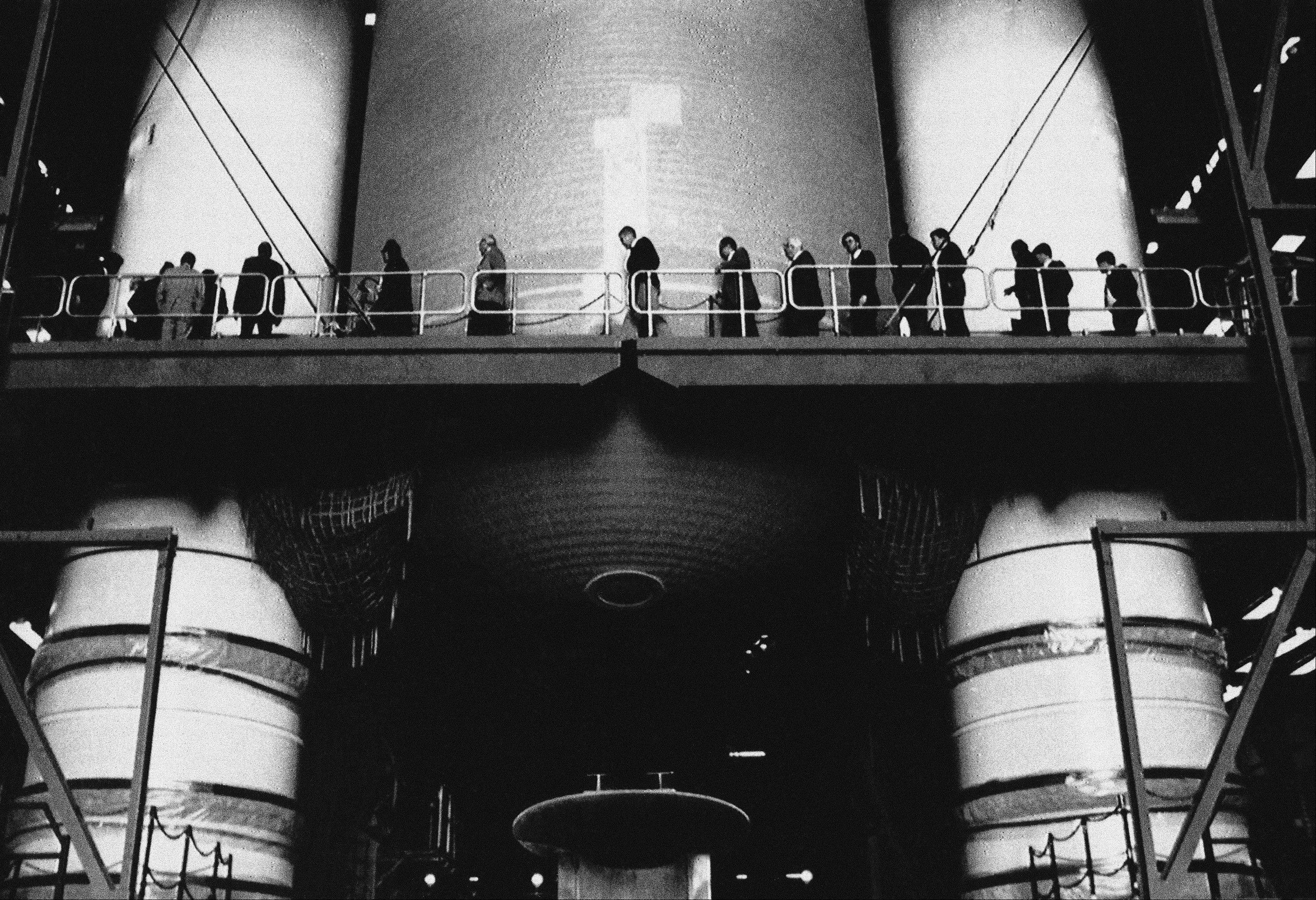 Members of the Presidential Commission on the Space Shuttle Challenger Accident walk past the external tank and solid rocket boosters of a shuttle being fitted in the Vehicle Assembly building at Kennedy Space Center in Cape Canaveral, Fla.