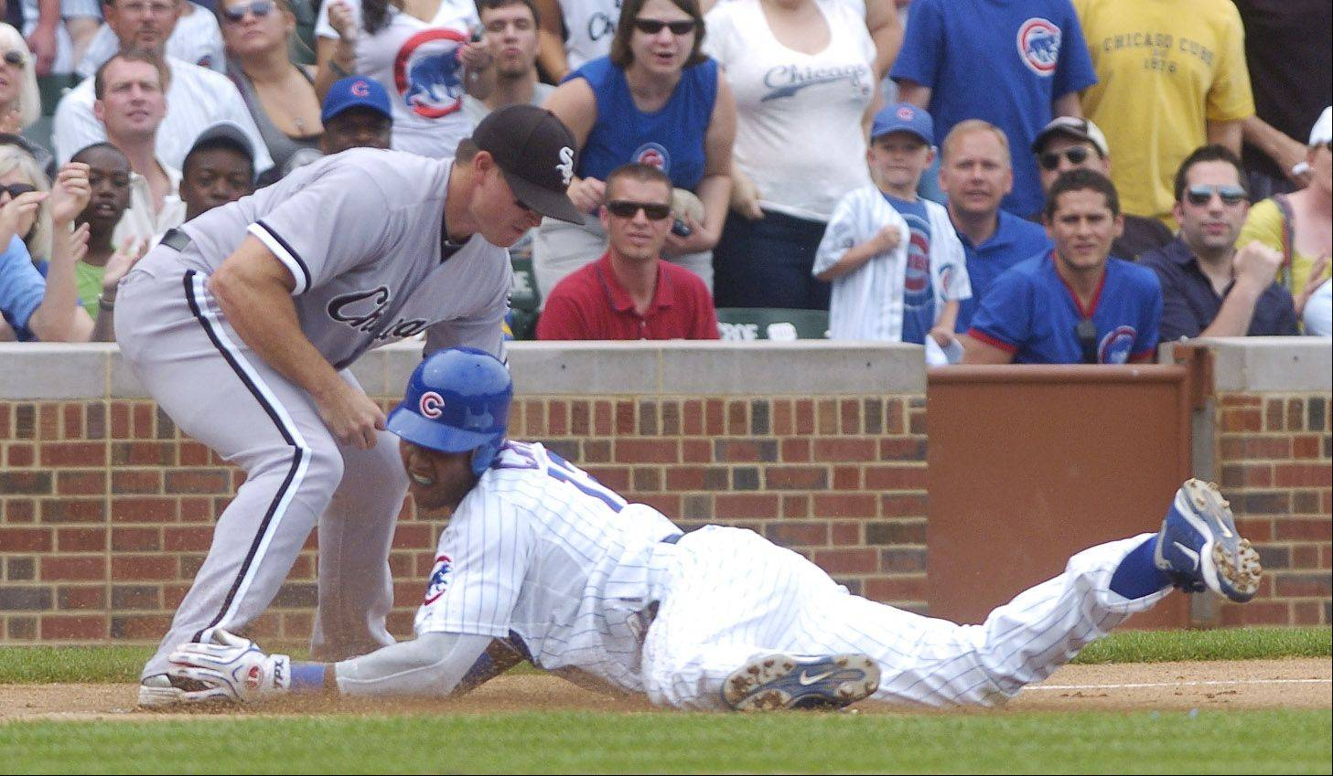 Starlin Castro of the Cubs is called safe on a close play at third for a fourth-inning triple as White Sox third baseman Mark Teahen applies the tag during Sunday's game.