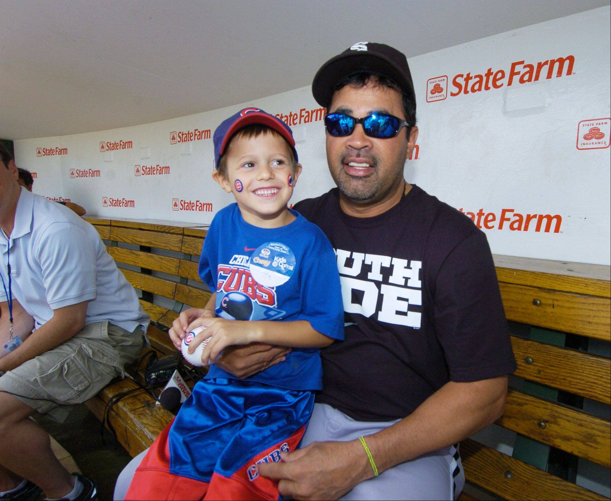 White Sox Manager Ozzie Guillen stops his interview with the media to have his photo taken with Trevor Anglin, 6, of Carterville, Ill. before Sunday's game at Wrigley Field. Anglin was sent into the dugout by Cubs General Manager Jim Hendry as a gentle prank on Guillen.