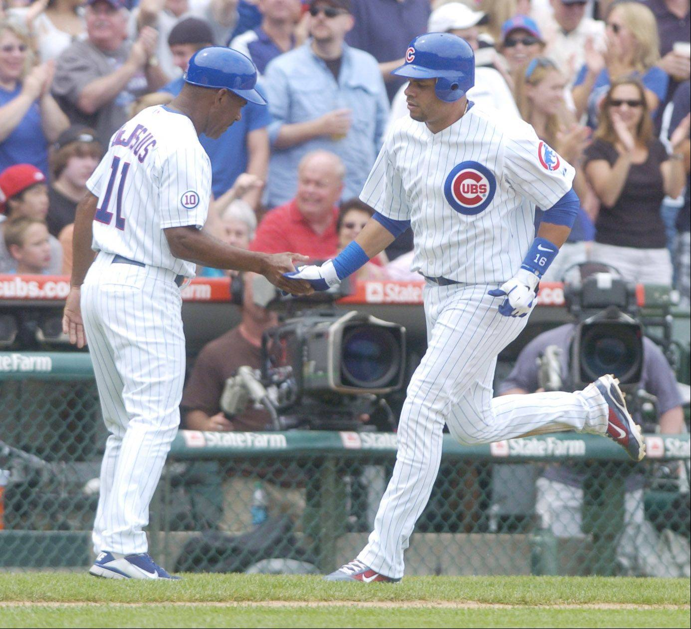 Aramis Ramirez of the Cubs is congratulated by third base coach Ivan DeJesus after his fourth inning home run during Sunday's game against the White Sox at Wrigley Field.