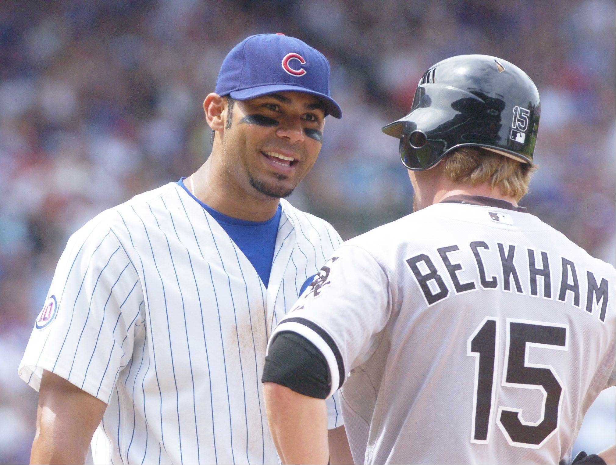 Cubs first baseman Carlos Pena chats with Gordon Beckham of the White Sox during Sunday's game at Wrigley Field.