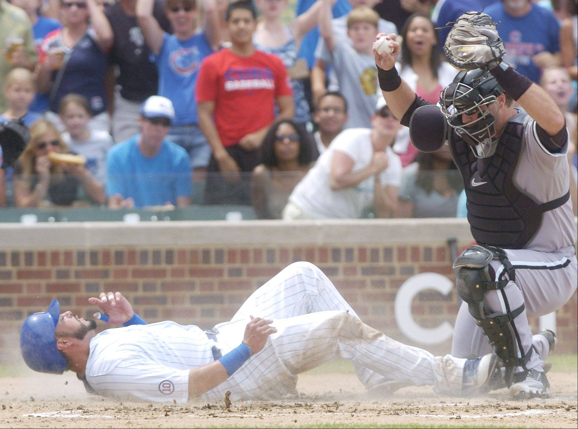 Geovany Soto of the Cubs winds up on his back after getting tagged out at the plate by White Sox catcher A.J. Pierzynski to end the third inning of Sunday's game at Wrigley Field.