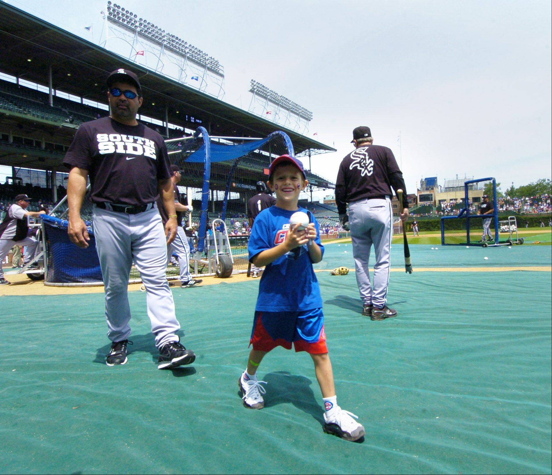 White Sox Manager Ozzie Guillen walks off the field with Cubs fan Trevor Anglin, 6, of Carterville, Ill. after giving him a quick tour of the Sox's batting practice before Sunday's game at Wrigley Field.
