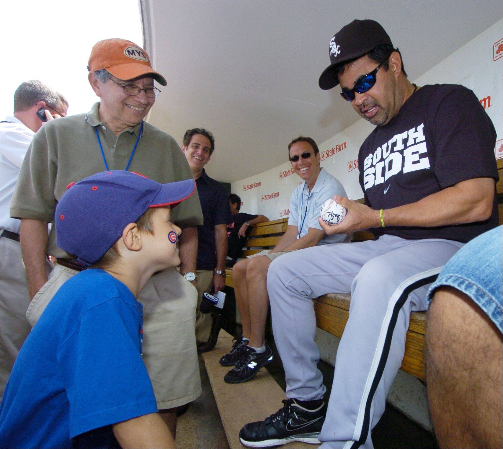 White Sox Manager Ozzie Guillen stops his interview with the media to sign a ball for Trevor Anglin, 6, of Carterville, Ill. before Sunday's game at Wrigley Field. Anglin was sent into the dugout by Cubs General Manager Jim Hendry as a gentle prank on Guillen.