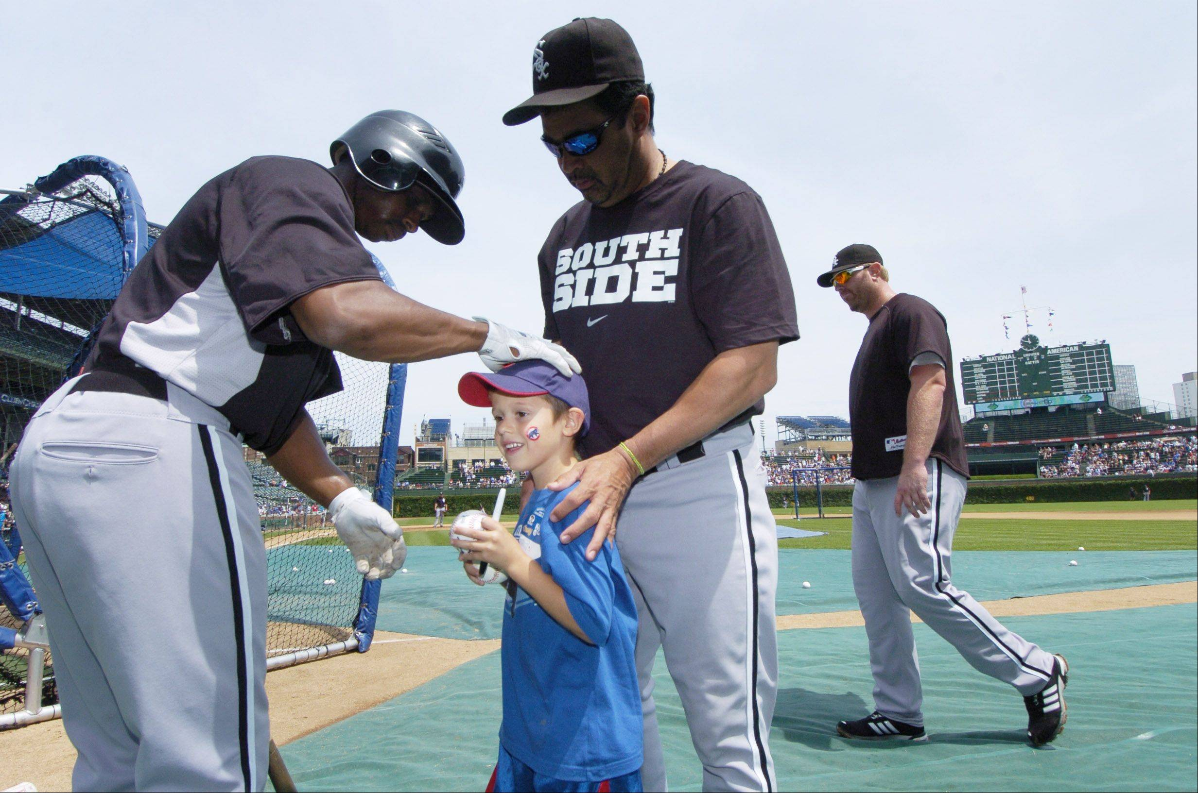 "White Sox Manager Ozzie Guillen, right, introduces Cubs fan Trevor Anglin, 6, of Carterville, Ill. to Sox leadoff hitter Juan Pierre before Sunday's game at Wrigley Field. Anglin was sent into the Sox dugout by Cubs General Manager Jim Hendry, and Guillen ran with the prank and gave the youth a quick ""tour."""