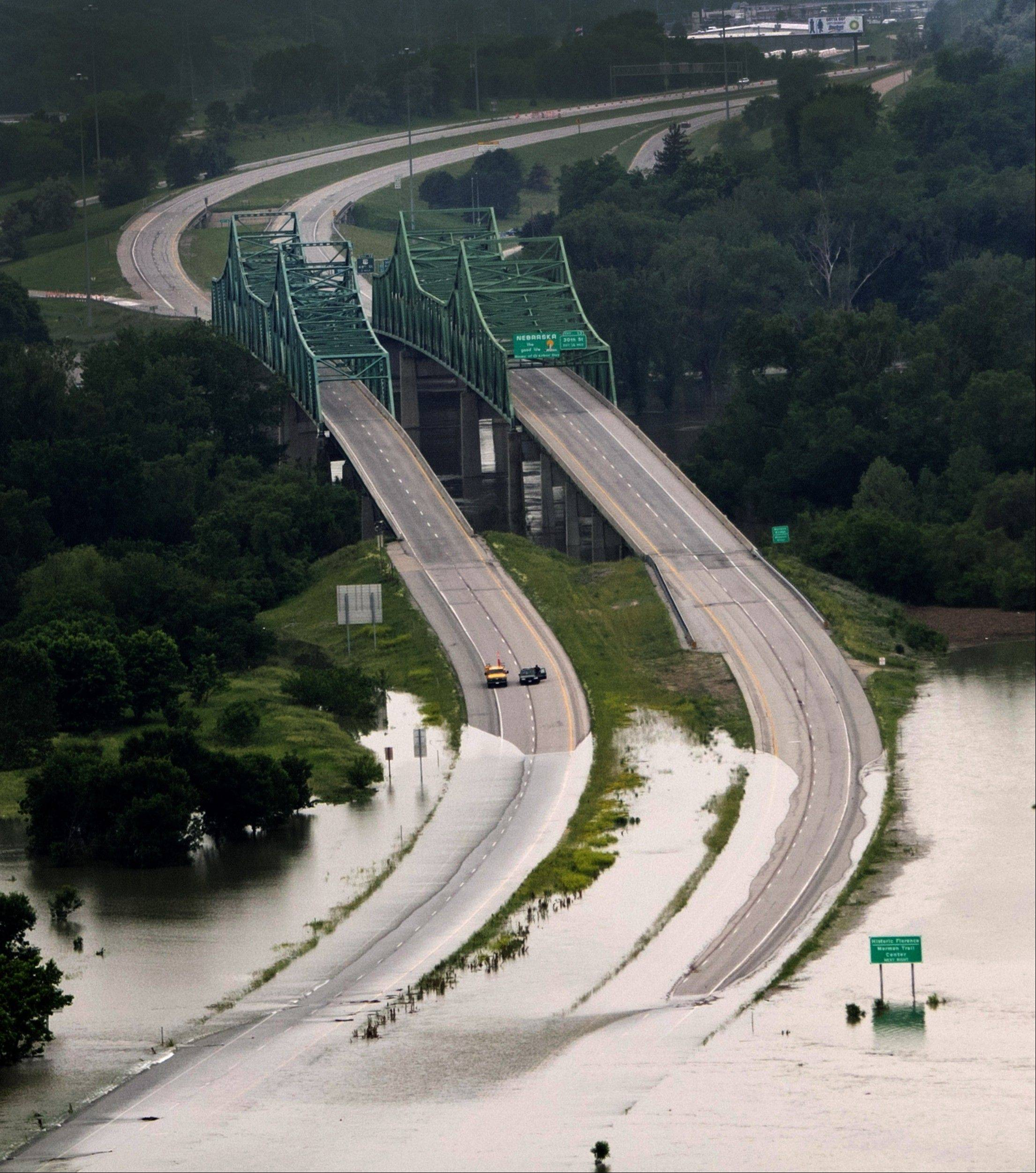 Interstate 680, which connects Omaha, Neb., with Iowa at the Mormon Bridge, was flooded last month on the Iowa side, The tornadoes and floods that pummeled much of the South and Midwest also have dealt a serious blow to struggling state budgets. The storms could force new cuts to education and other services to offset hundreds of millions of dollars in disaster aid.