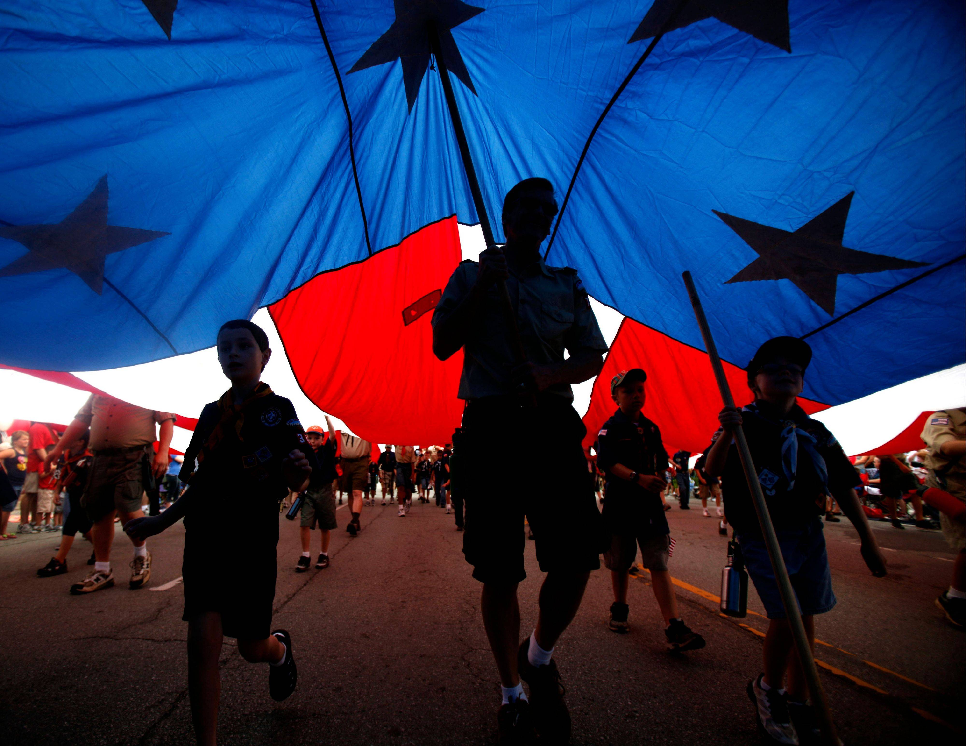 Boy Scouts of America and Cub Scout troops carry a large American flag during the LibertyFest Fourth of July parade in Edmond, Okla., Monday, July 4, 2011.