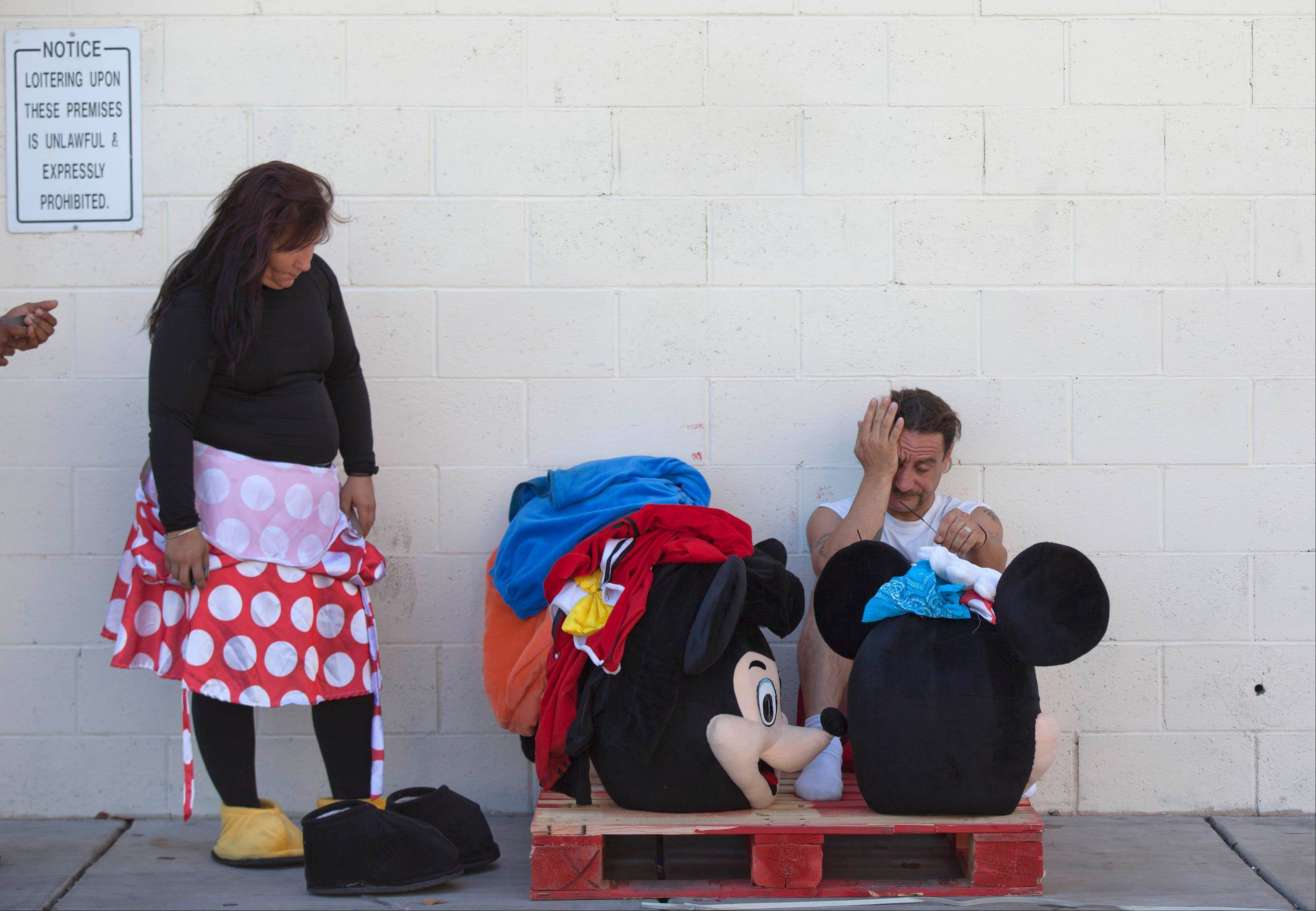 Robyn Vanderlip, left, and James Miller take a break behind a restaurant along The Strip after several hours of posing as Minnie and Mickey Mouse for tips from Las Vegas tourists in June.