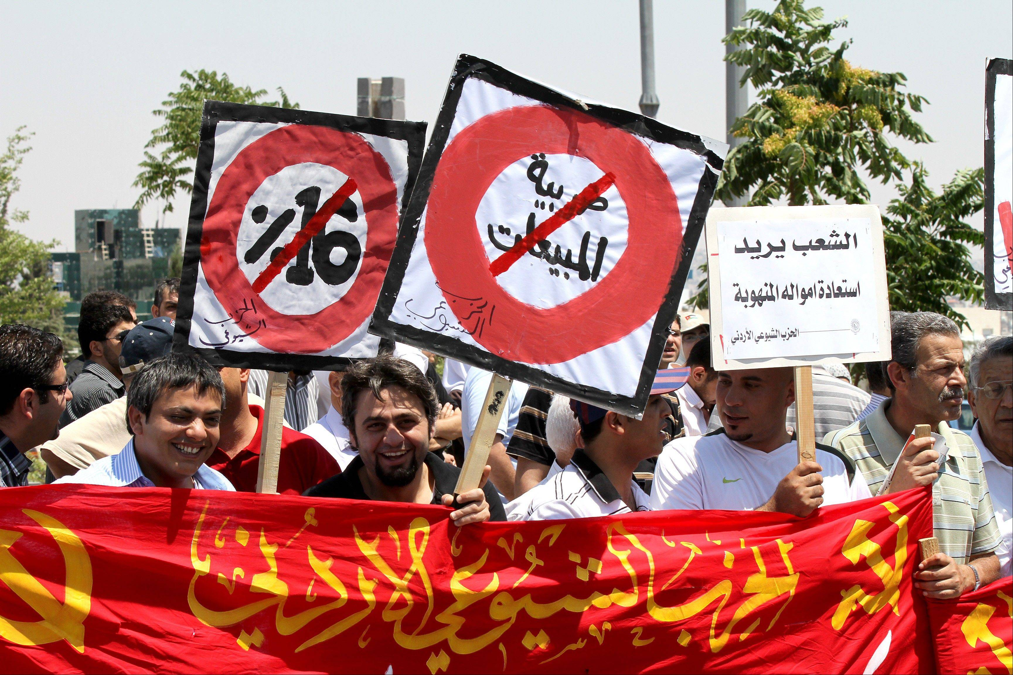 "Supporters of the Communist party holds banners demanding of cancellation of the sales tax during a demonstration by opposition parties demanding an end to government corruption in front of the prime minister's office in Amman, Jordan. White placard on right reads, ""People want the stolen money back."" The unrest of the Arab Spring has thrown much of the Middle East into turmoil, but a handful of countries have found ways to prevent or calm the anger of the streets. At the heart of the political standoff in Jordan is a half-British king and darling of Western governments who is trying to avoid the tumult."