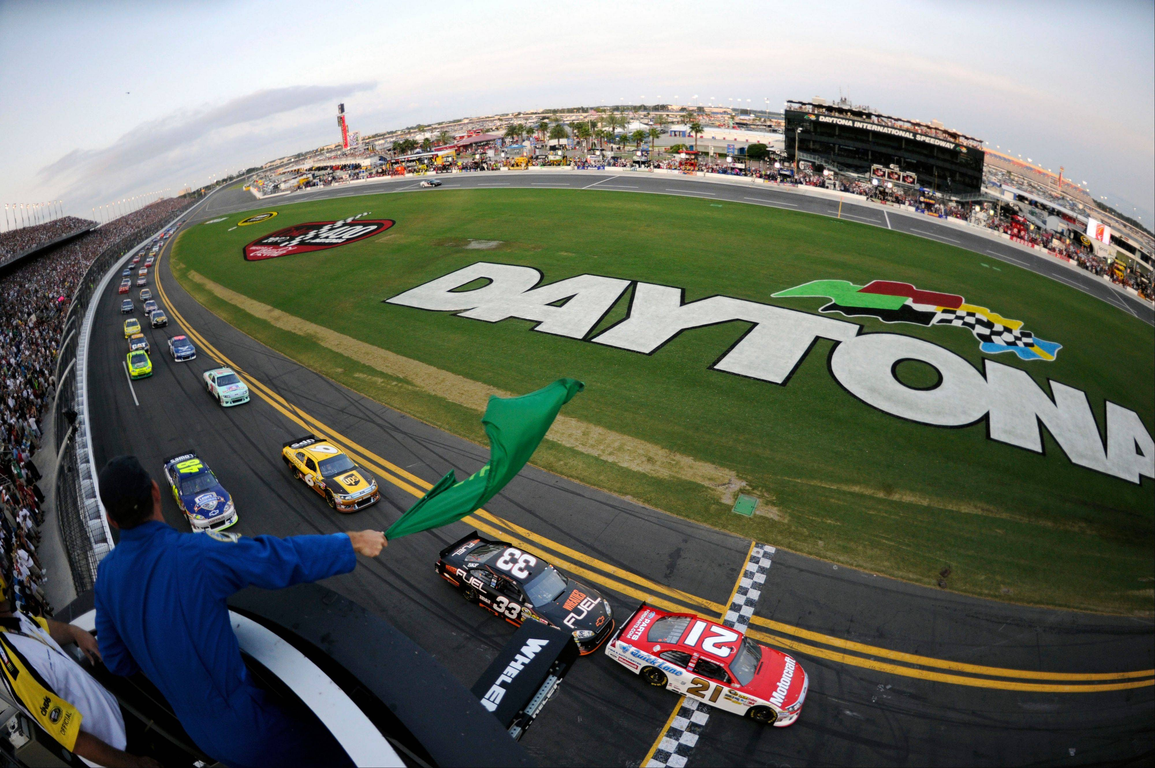 In this image made with a fisheye lens, NASA astronaut Tony Antonelli, left, waves the green flag to start the Coke Zero 400 NASCAR auto race at Daytona International Speedway in Daytona Beach, Fla., Saturday.