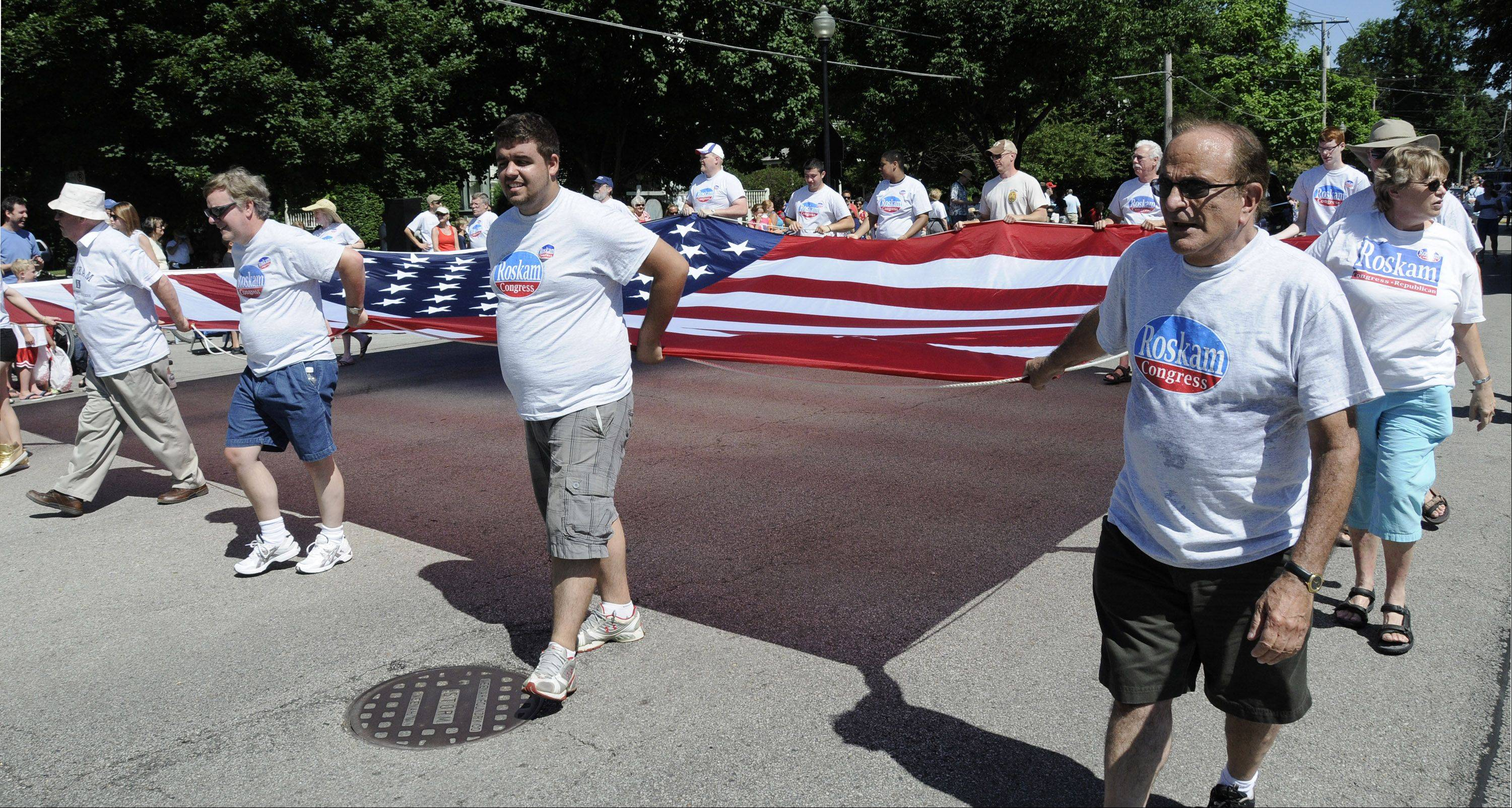 Friends and supporters of Republican Congressman Peter Roskam work to carry a large flag in Wheaton's Independence Day parade.
