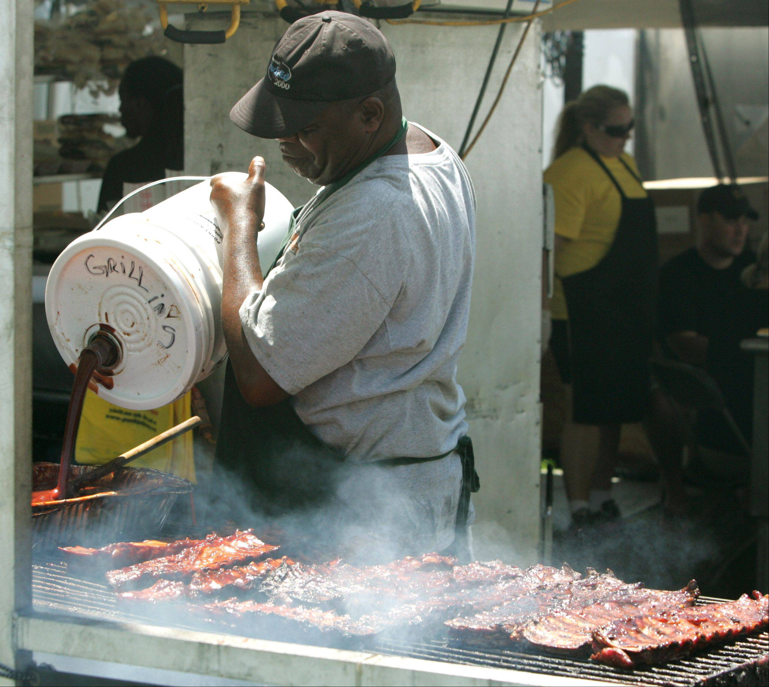 Cornell Simon heats barbecue sauce during the final day of Naperville's Ribfest. Simon is from Porky N Beans of Port Saint Lucie, Florida.