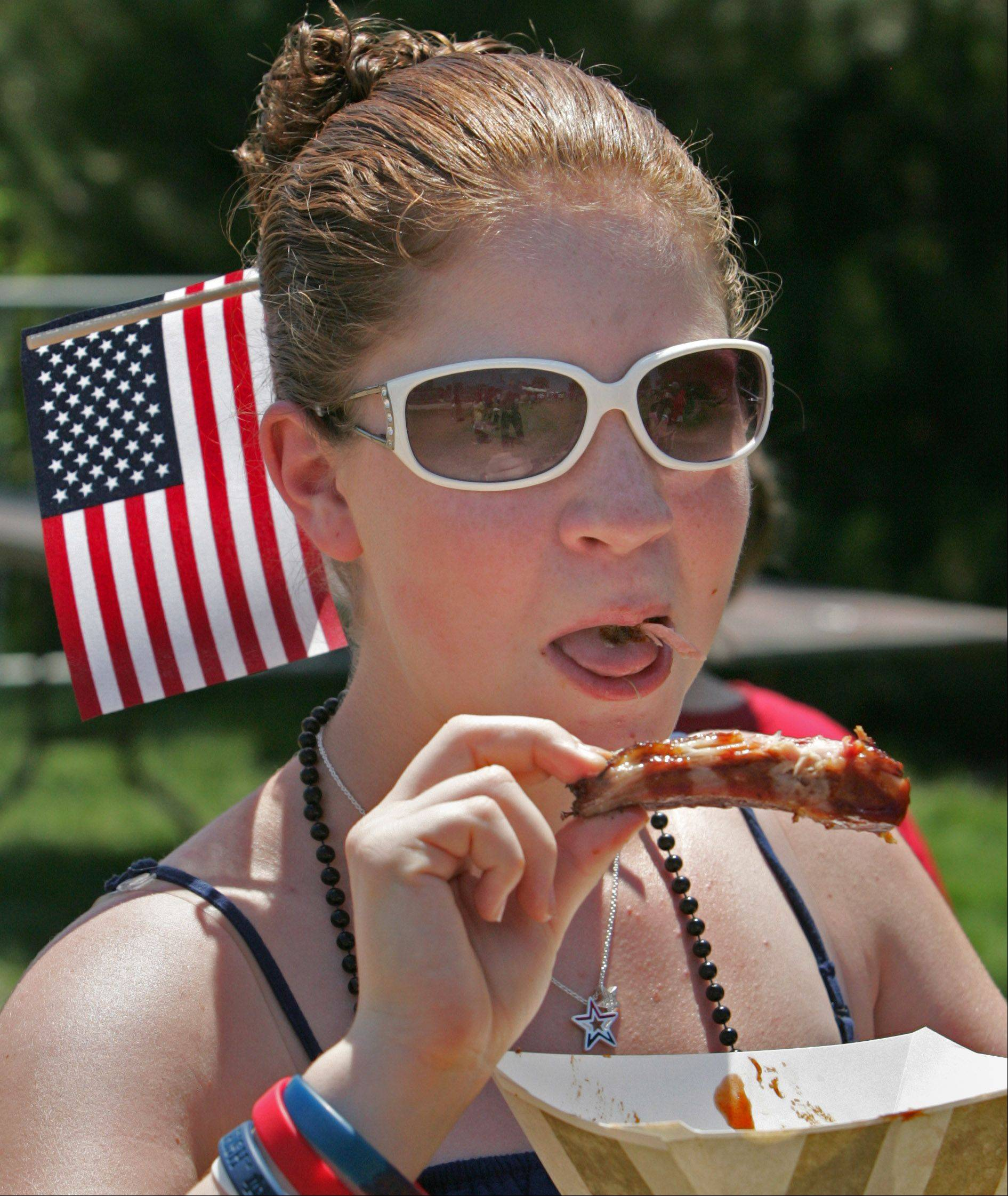Carolyn Angiollo, 14, of Palatine enjoys eating a rib during the final day of Naperville's Ribfest.