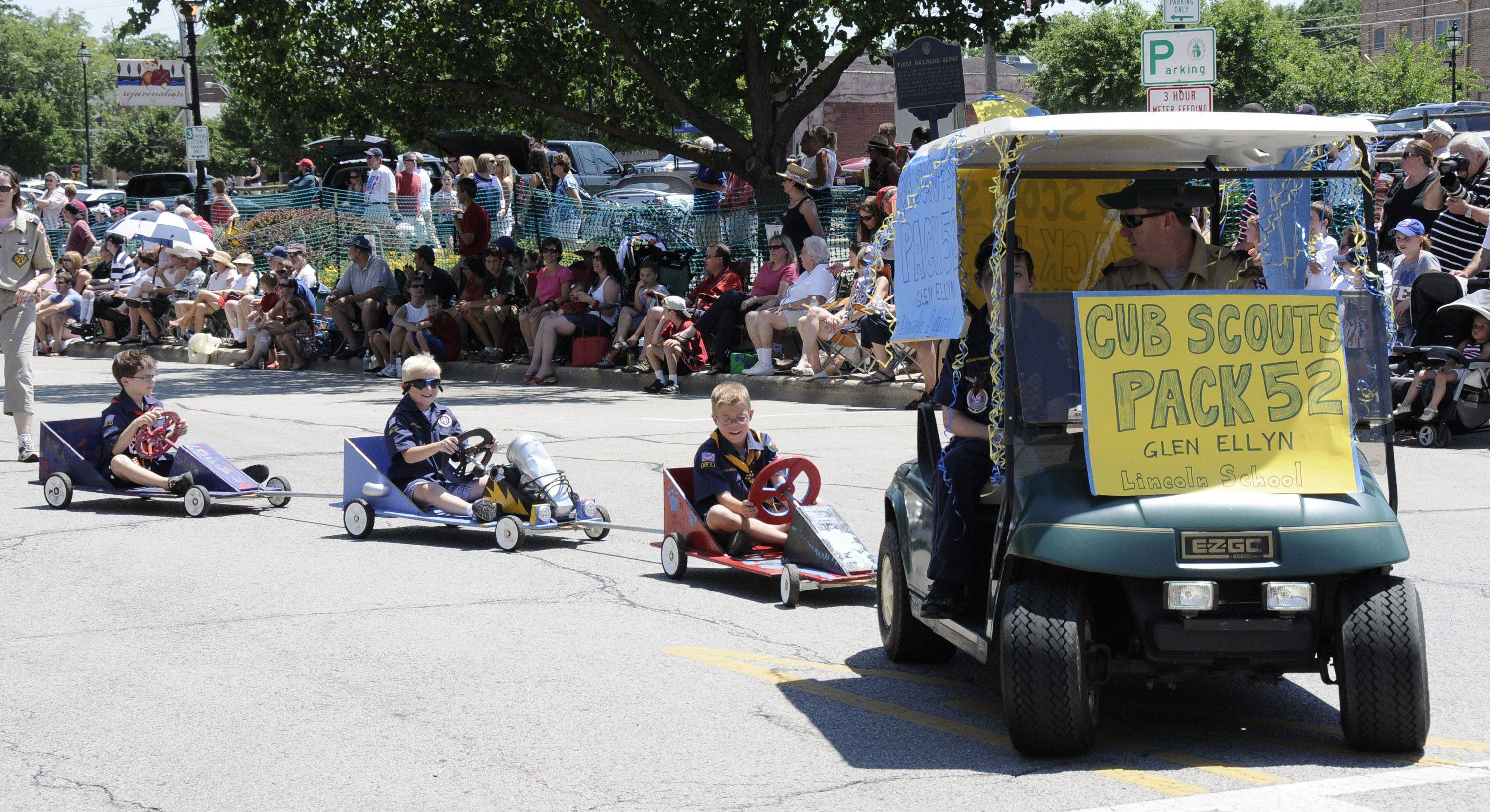 Cub Scouts from Glen Ellyn Pack 52 turn the corner in their go-carts onto Main Street in Glen Ellyn's Independence Day parade.