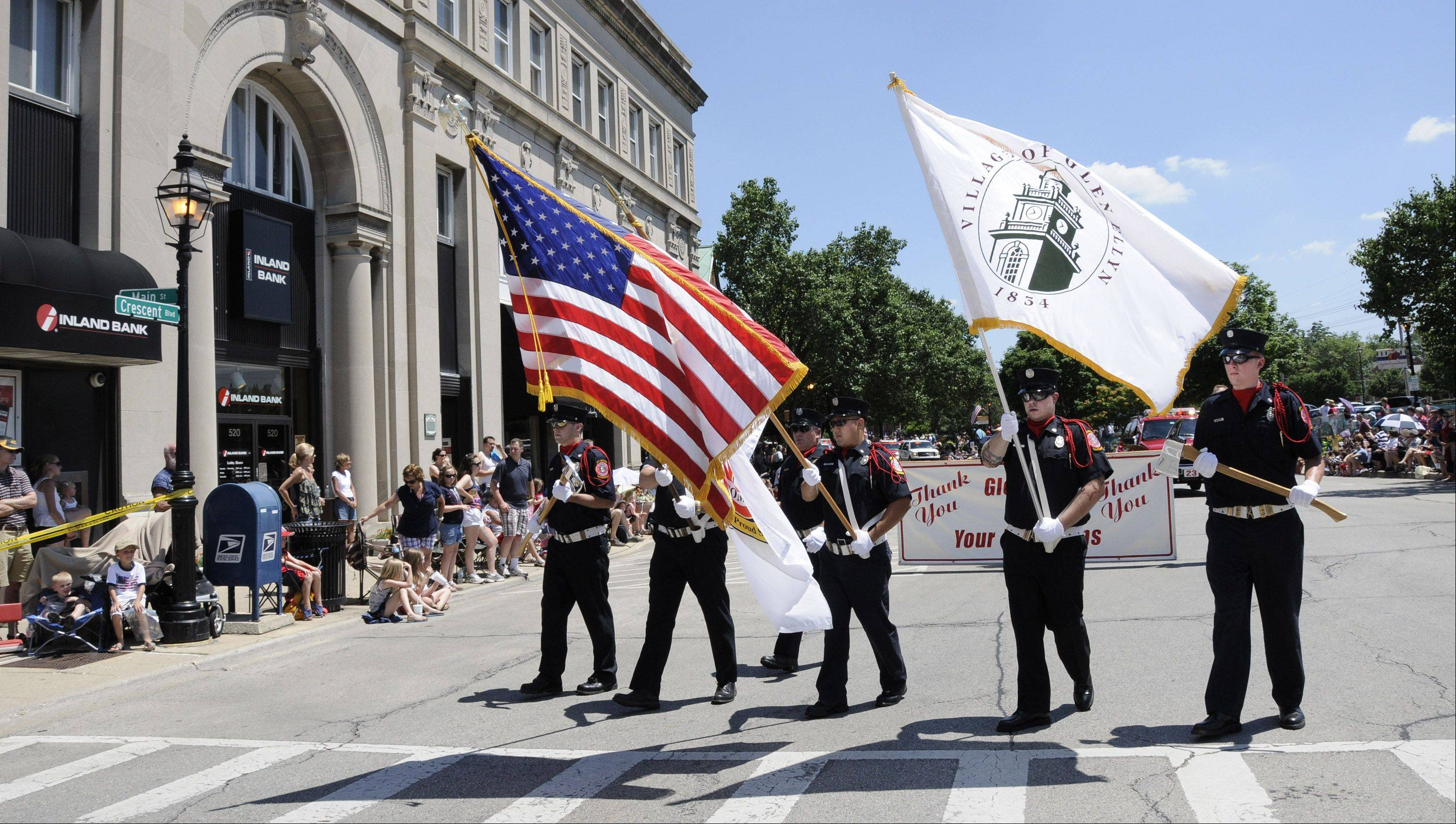 The Glen Ellyn Fire Department's color guard leads Glen Ellyn's Independence Day parade, followed by many of the department's fire engines with sirens blaring.
