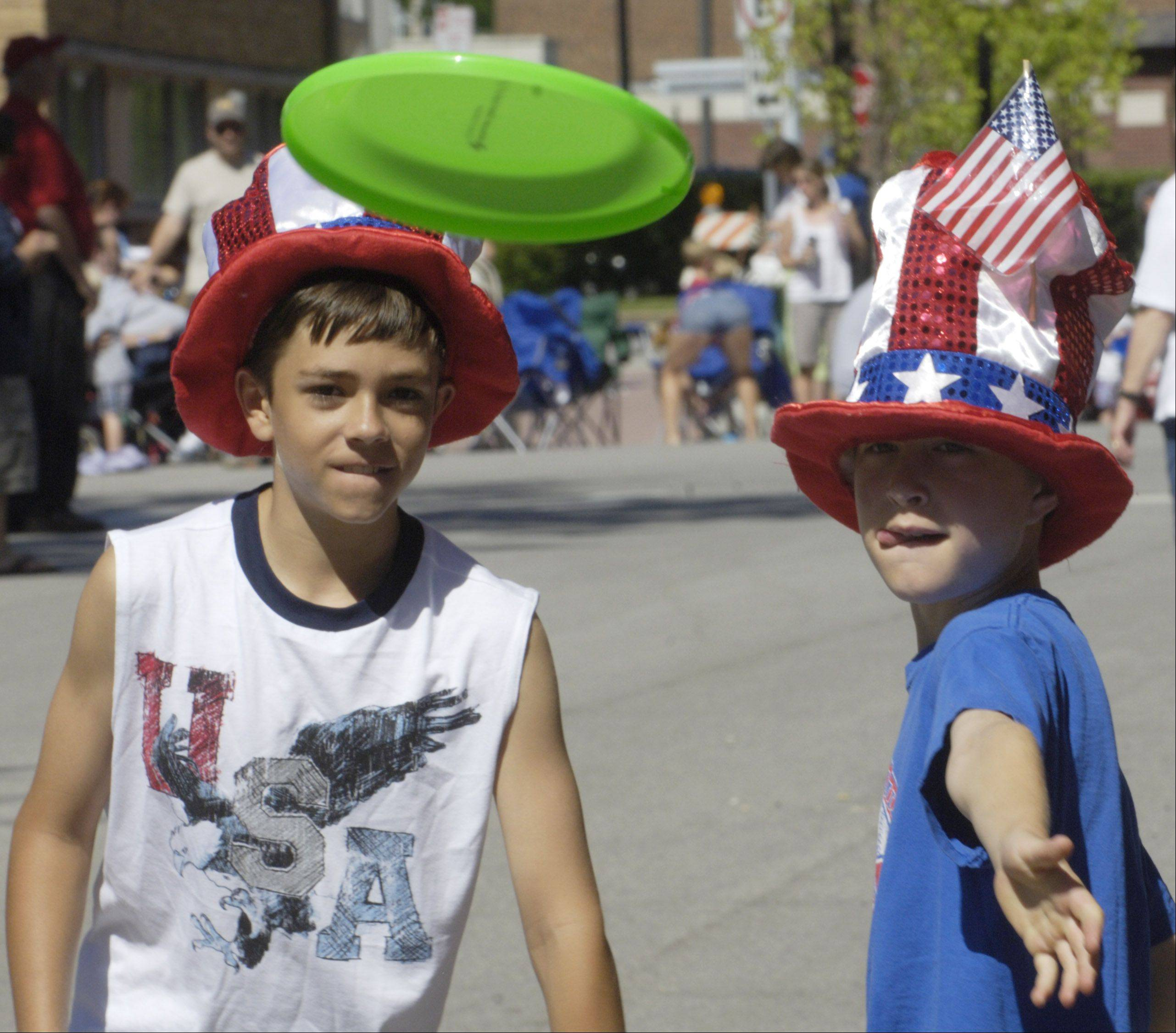 Leo Rule, 12, left and Tyler Frank, 11, both of Arlington Heights, toss a disc before the start of the Arlington Heights Fourth of July parade Monday.