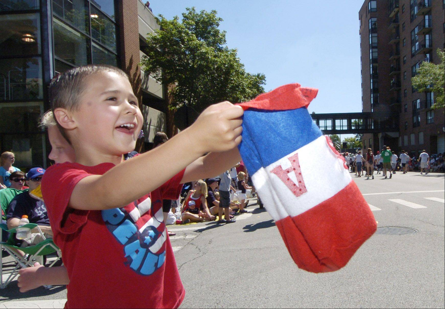 Drew Phillips, 5, of Arlington Heights catches candy in his Uncle Sam hat during the Arlington Heights Fourth of July parade Monday.