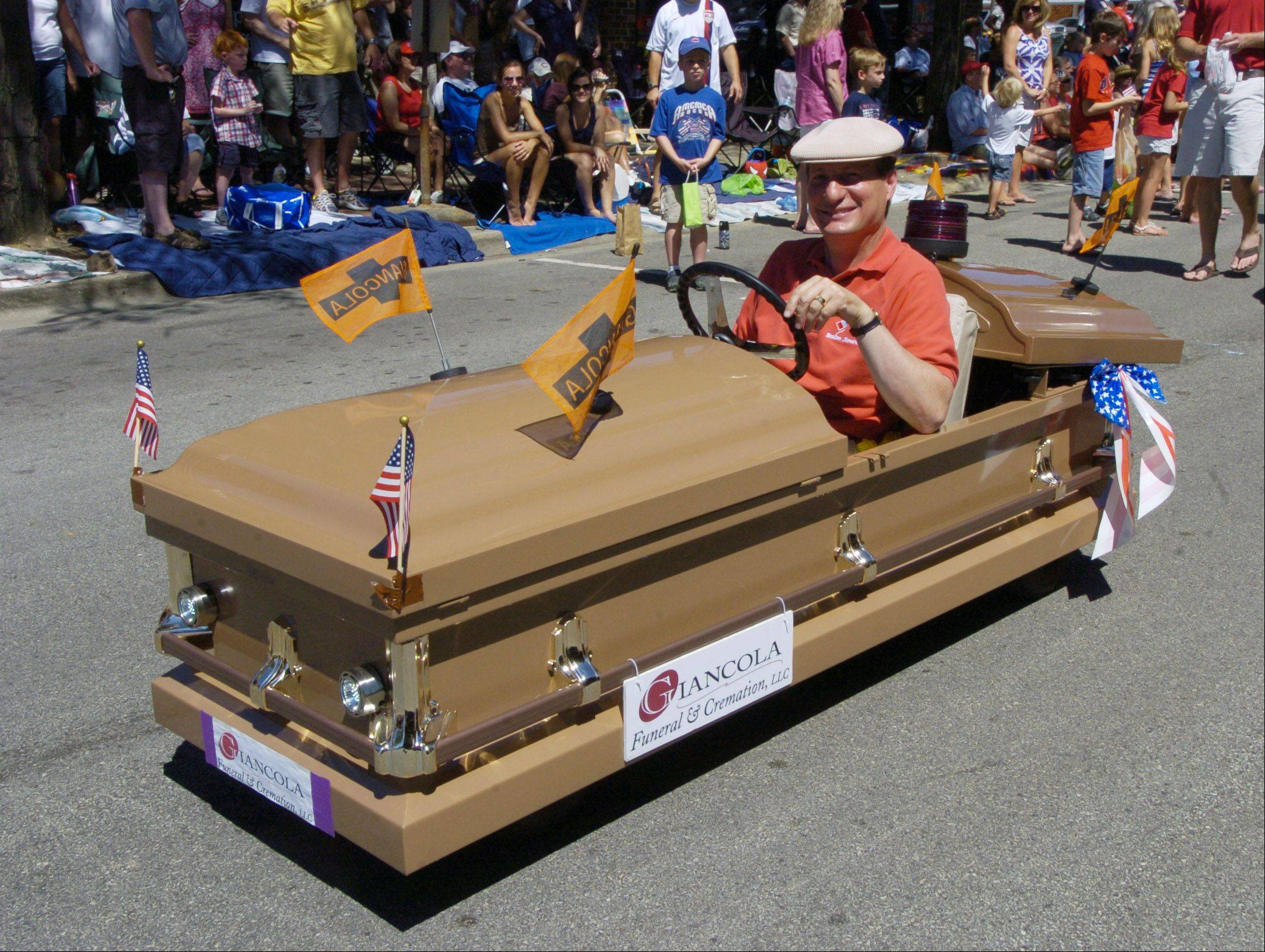 It's no ordinary float. Mark Giancola of Arlington Heights drives a casket during the parade Monday.